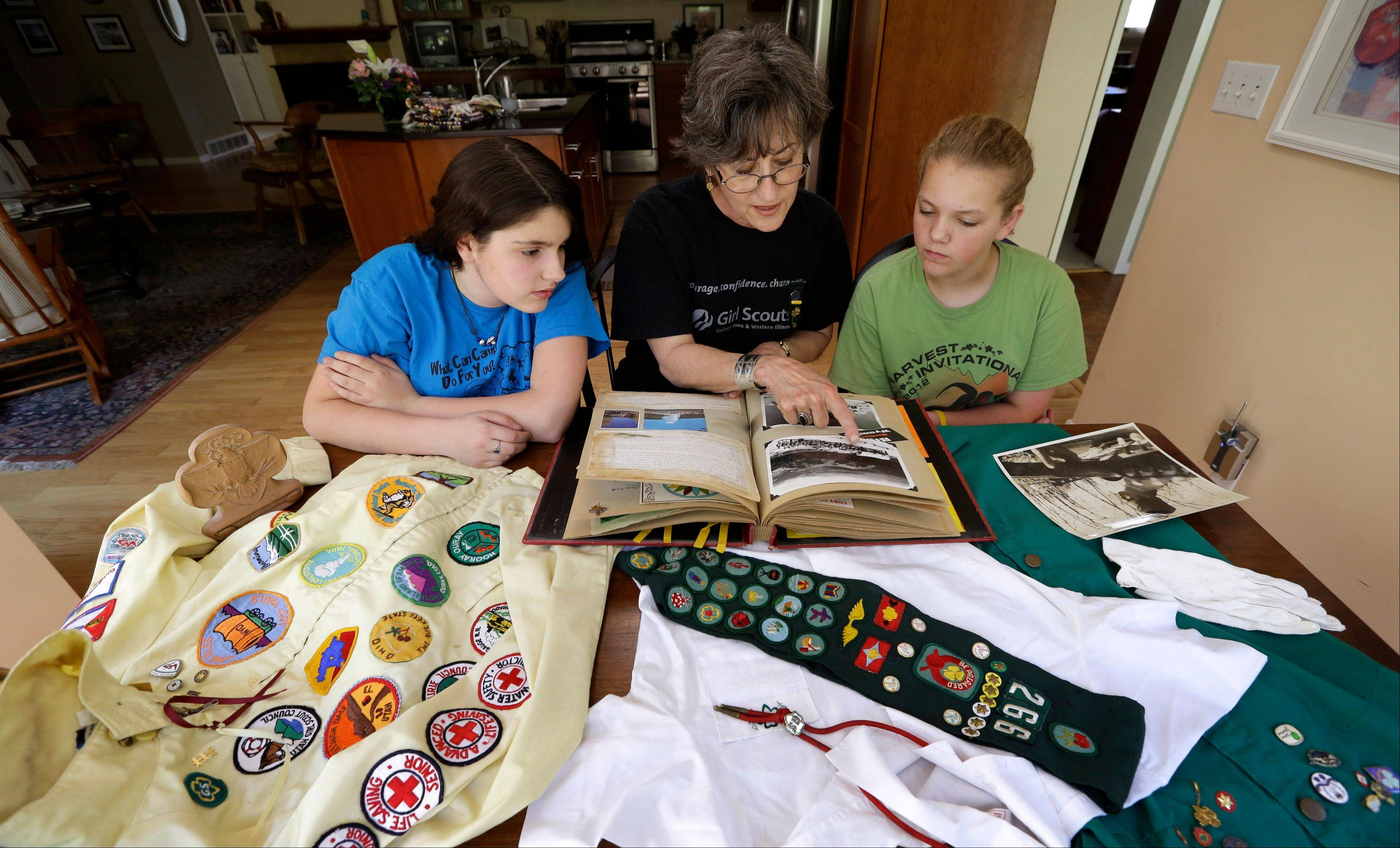 In this Tuesday, May 14, 2013 photo, Joni Kinsey, of Iowa City, Iowa, shows some of her Girl Scouts memorabilia to two girls in her troop in Iowa City, Iowa. In an effort to save money, Girl Scout councils across the country are making proposals that would have been unthinkable a generation ago: selling summer camps that date back to the 1950s.