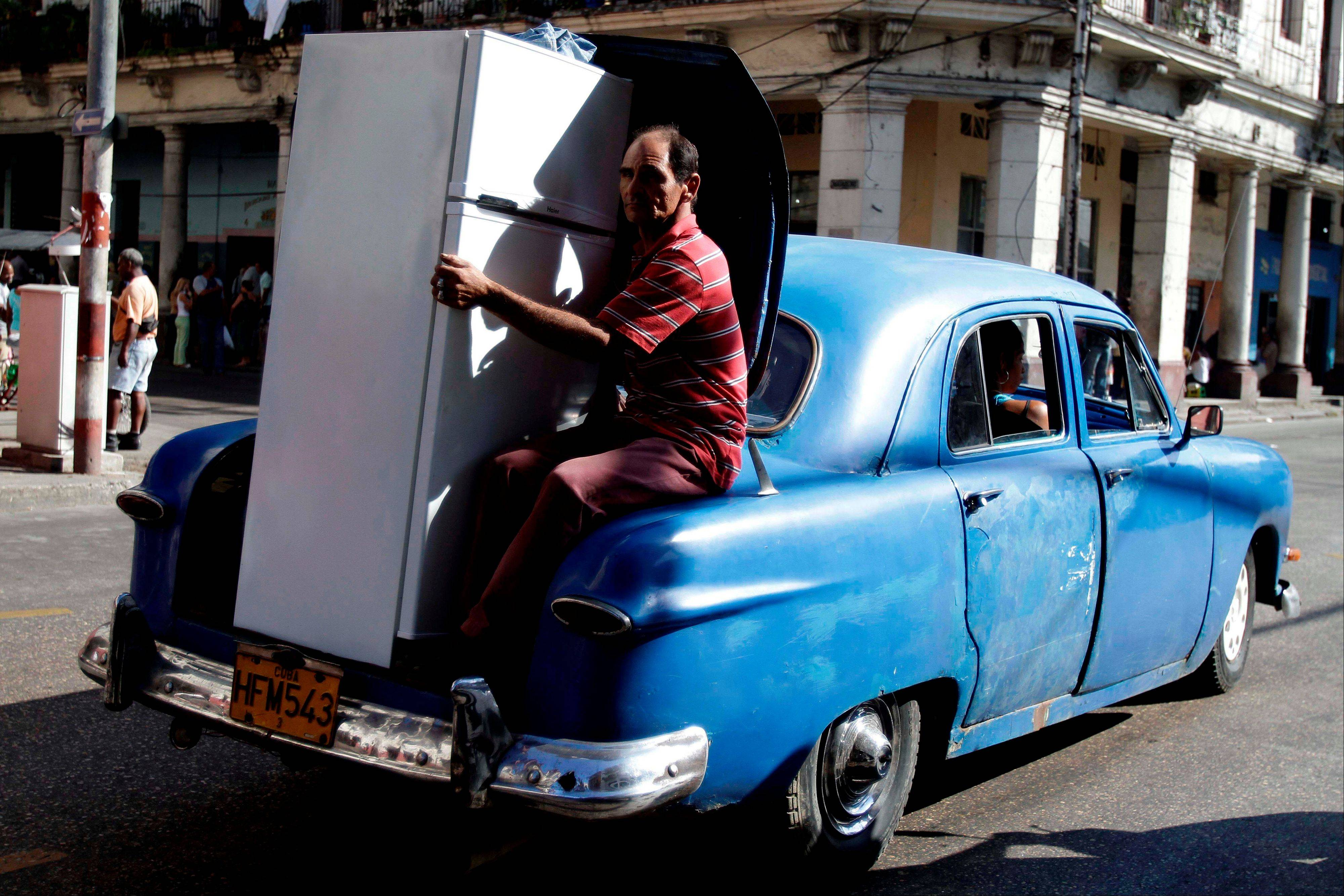 In this Feb. 14, 2012 file photo, a man transports a new Chinese made refrigerator in the trunk of a old car in Havana, Cuba. Cuba has authorized individual imports of appliances such as air conditioners, refrigerators and microwave ovens, lifting a ban imposed in 2005 amid a wave of energy shortages and blackouts.