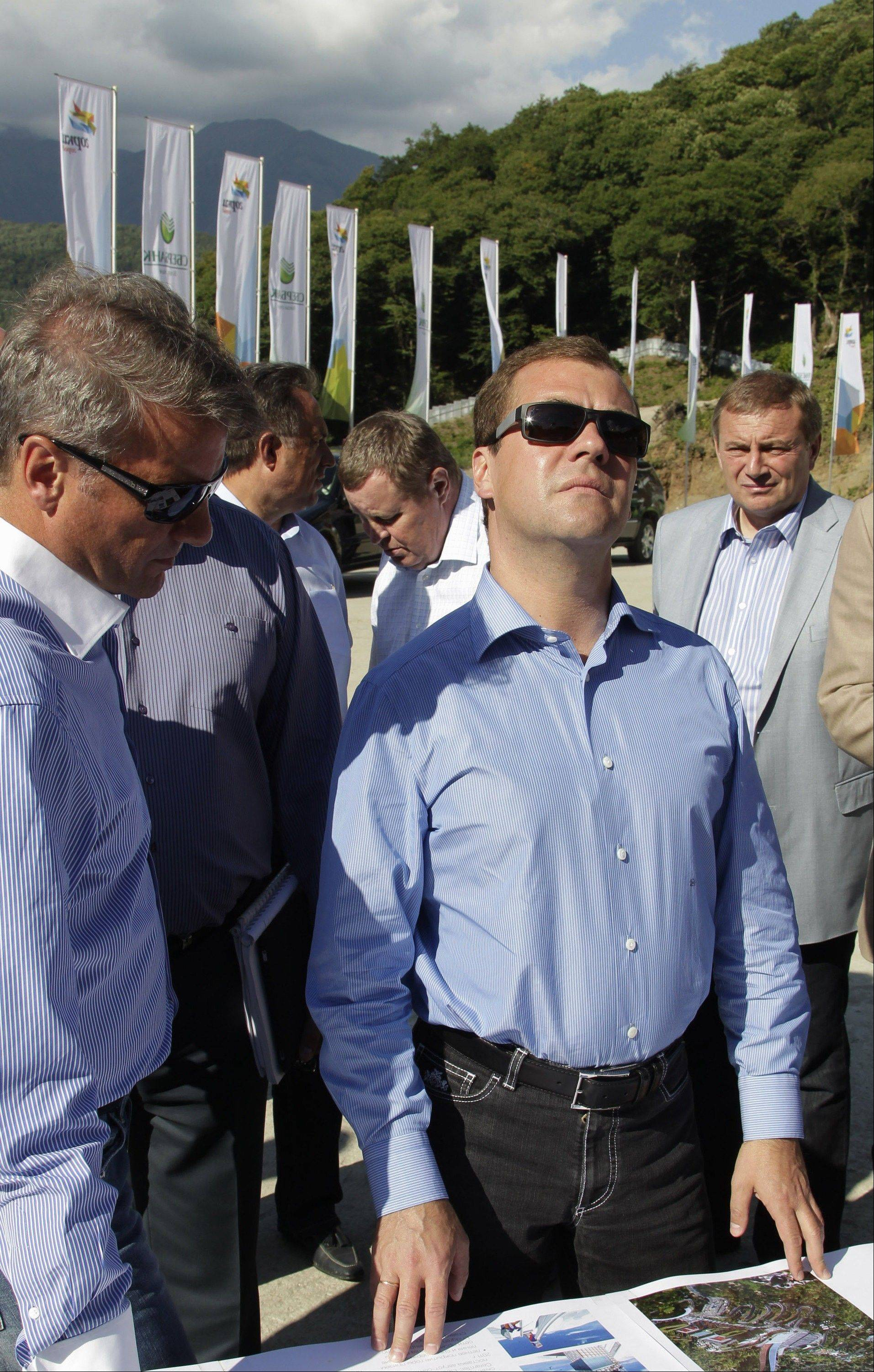 In this Aug. 23, 2011 photo, then, Russian President Dmitry Medvedev and Sberbank President German Gref, left, visit a construction site of a skiing facility for the 2014 Sochi Winter Olympics, near the Black Sea resort of Sochi, southern Russia.