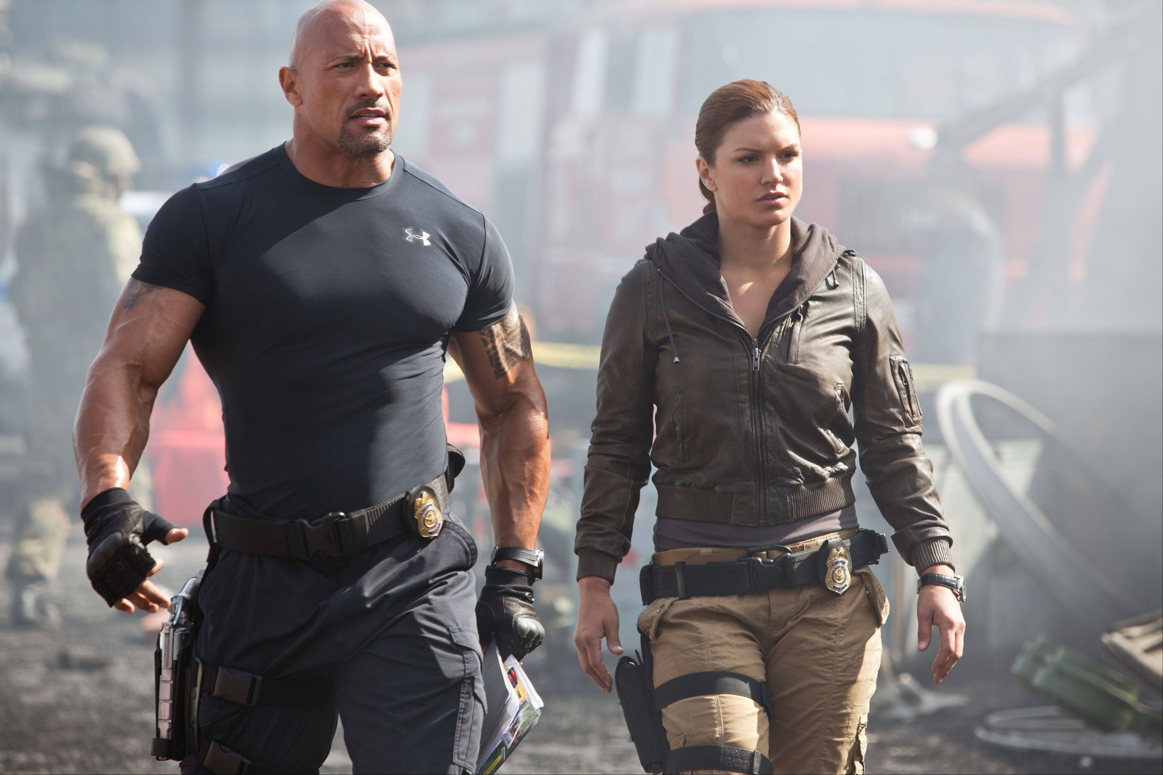 "Hobbs (Dwayne Johnson) and his fellow cop Riley (Gina Carano) seek a device worth billions of dollars in Justin Lin's thrill-packed ""Fast & Furious 6."" The film pulled in $98 million in its first weekend of release."