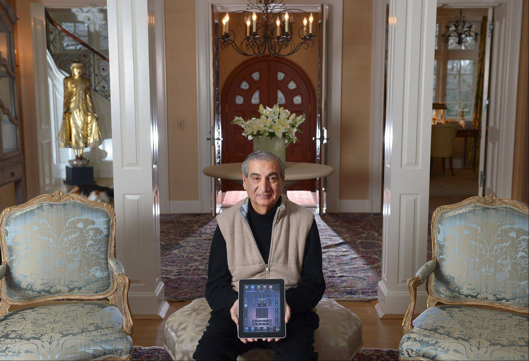 Choksi, 69, holds an iPad, which he uses to control devices in the home he shares with his wife, Mary.