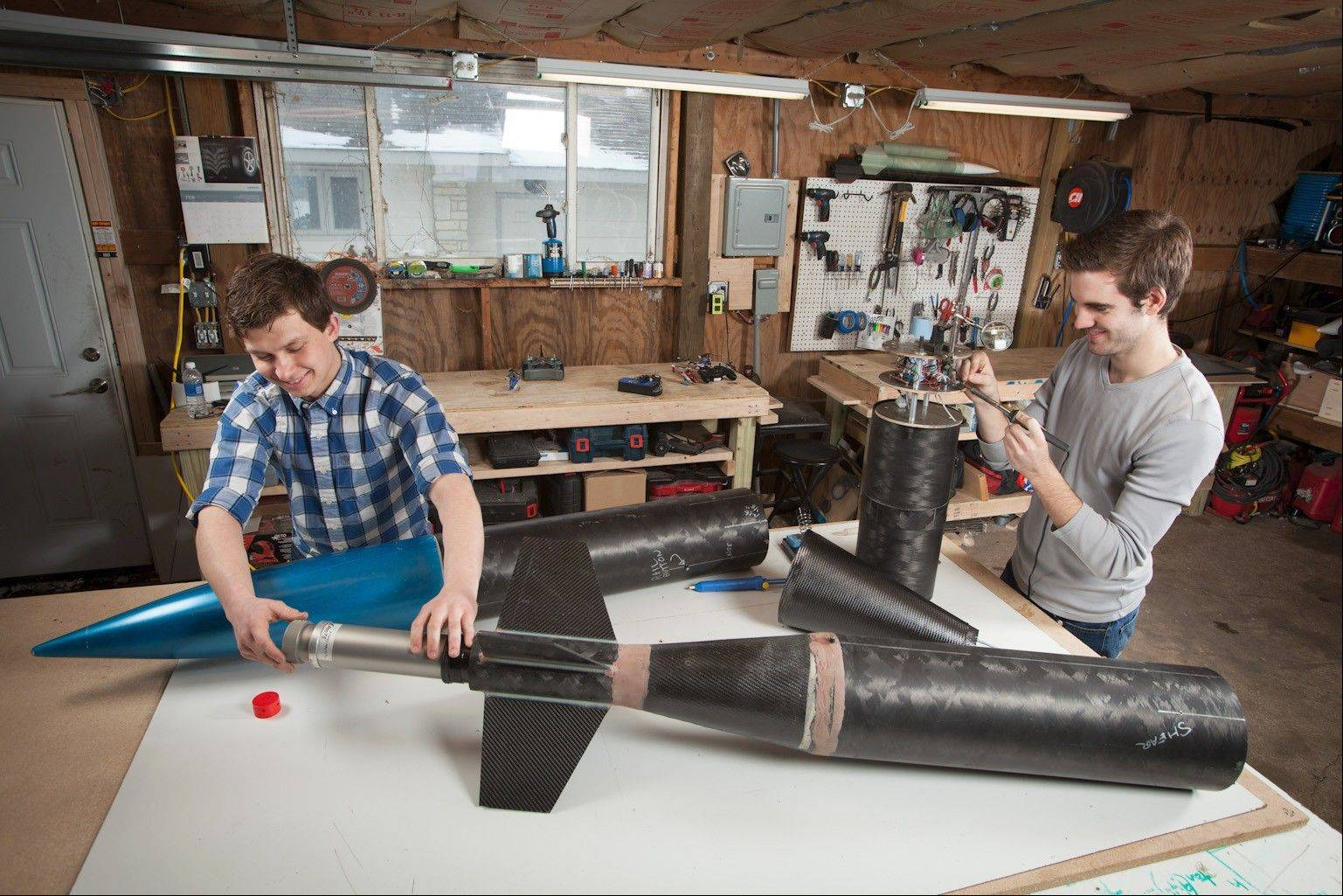 A team of five students from Harper College and three from DeVry recently placed fourth in the NASA University Student Launch Initiative.  Team Leader Scott Mueller, left, and Chris Wessel work on their rocket prior to the launch. Mueller, of Elk Grove Village, is a robotics expert and Wessel has plans to be a mechanical engineer.