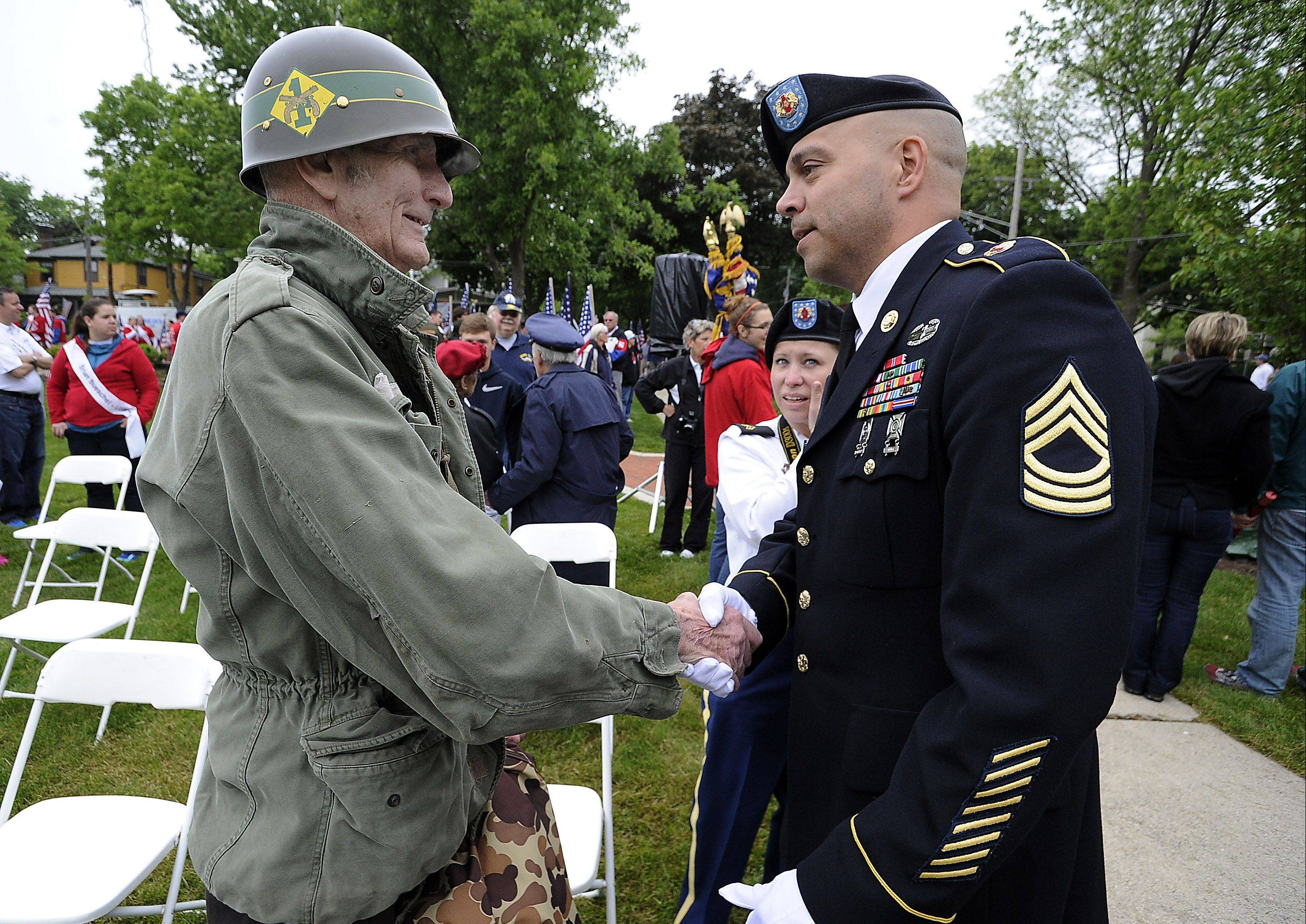 Korean War veteran Stan Mosher, 79, of Lombard, shakes the hand of Master Sgt. Gilbert Garrett of Arlington Heights, who served in Iraq and is secretary of the general staff for the 85th U.S. Army Reserve Support Command. The men were among a few hundred who attended the Arlington Heights Memorial Day ceremony on Monday in Memorial Park.