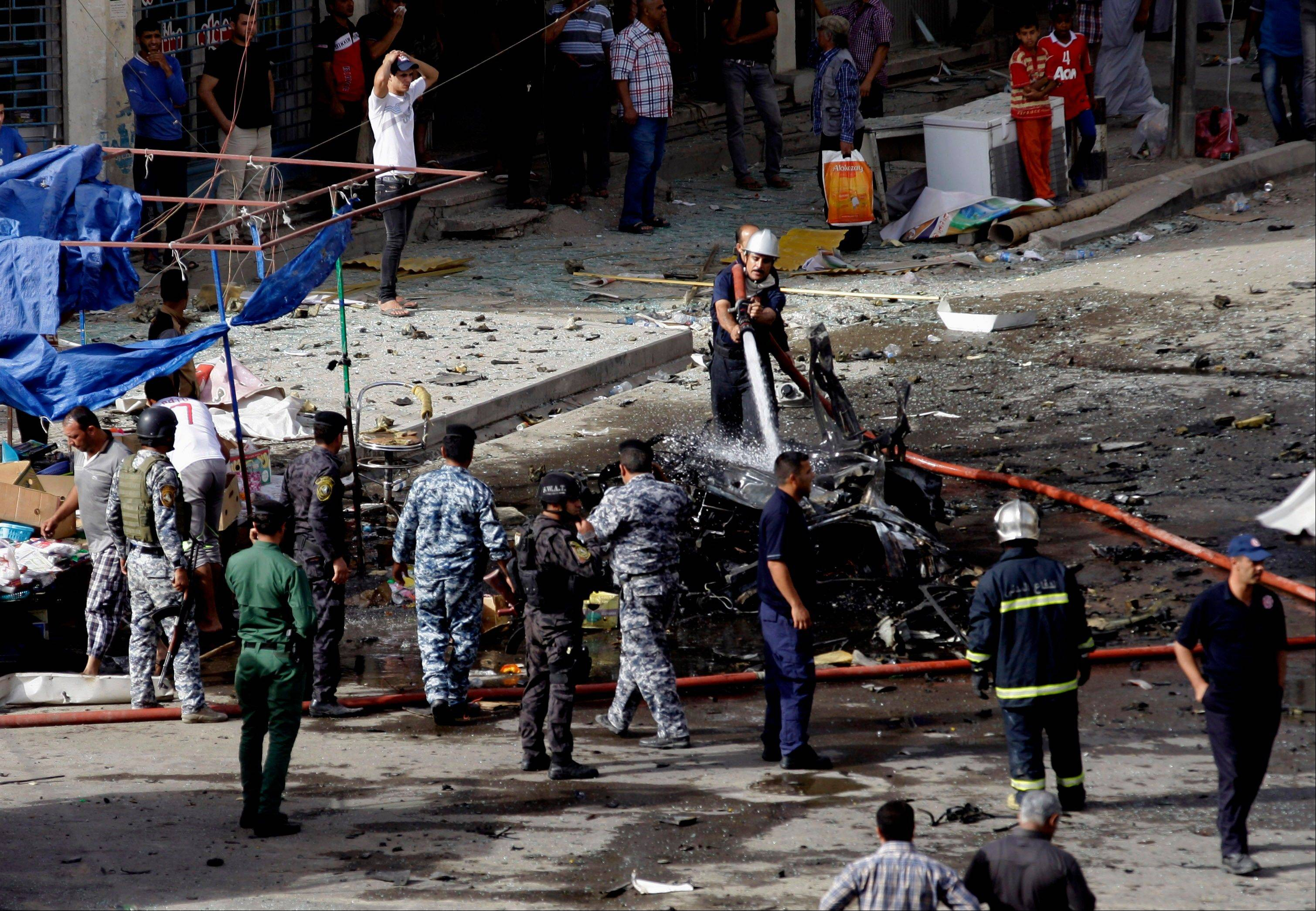 Security forces inspect the scene of a car bomb attack in the Baghdad, Iraq, Monday, May 27, 2013. A parked car bomb explosion in the busy commercial Sadoun Street in central Baghdad, killed and wounded scores of people, police said.