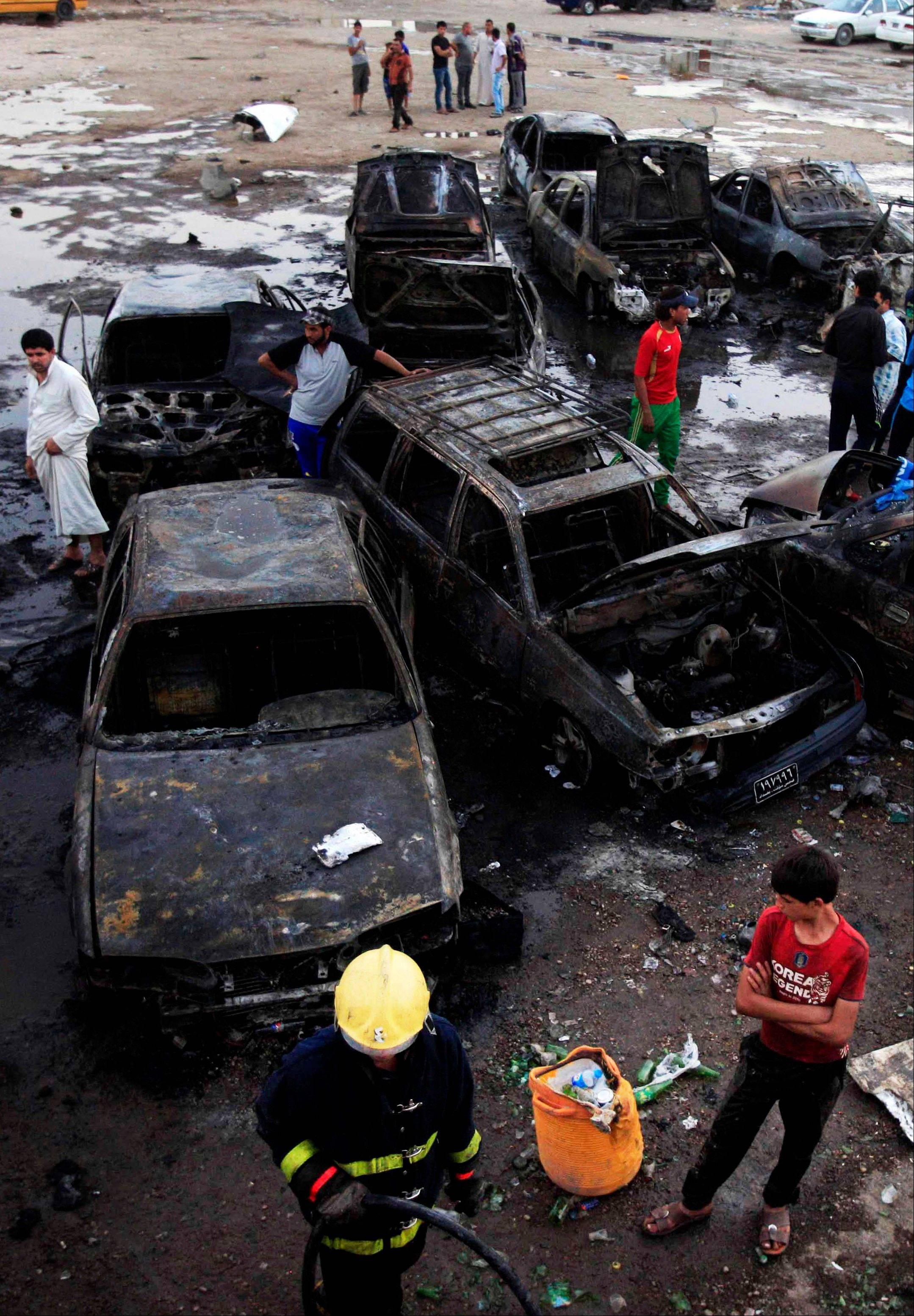 Iraqis gather at the scene of a car bomb attack at a used cars dealers parking lot in Habibiya neighborhood of eastern Baghdad, Iraq, Monday, May 27, 2013. A wave of car bombings tore through mostly Shiite Muslim neighborhoods of the Baghdad area, killing and wounding dozens of people, police said, in the latest outburst of an unusually intense wave of bloodshed roiling Iraq. The blasts are the latest indication that Iraq's security is rapidly deteriorating.