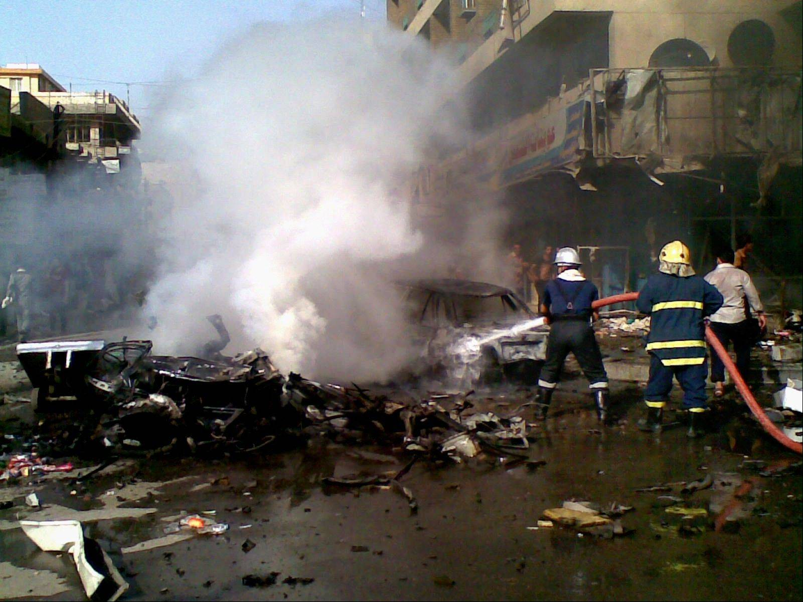 Iraqi firefighters distinguish a fire at the scene of a car bomb attack in Baghdad, Iraq, Monday, May 27, 2013. A parked car bomb explosion in the busy commercial Sadoun Street in central Baghdad, killed and wounded scores of people, police said.