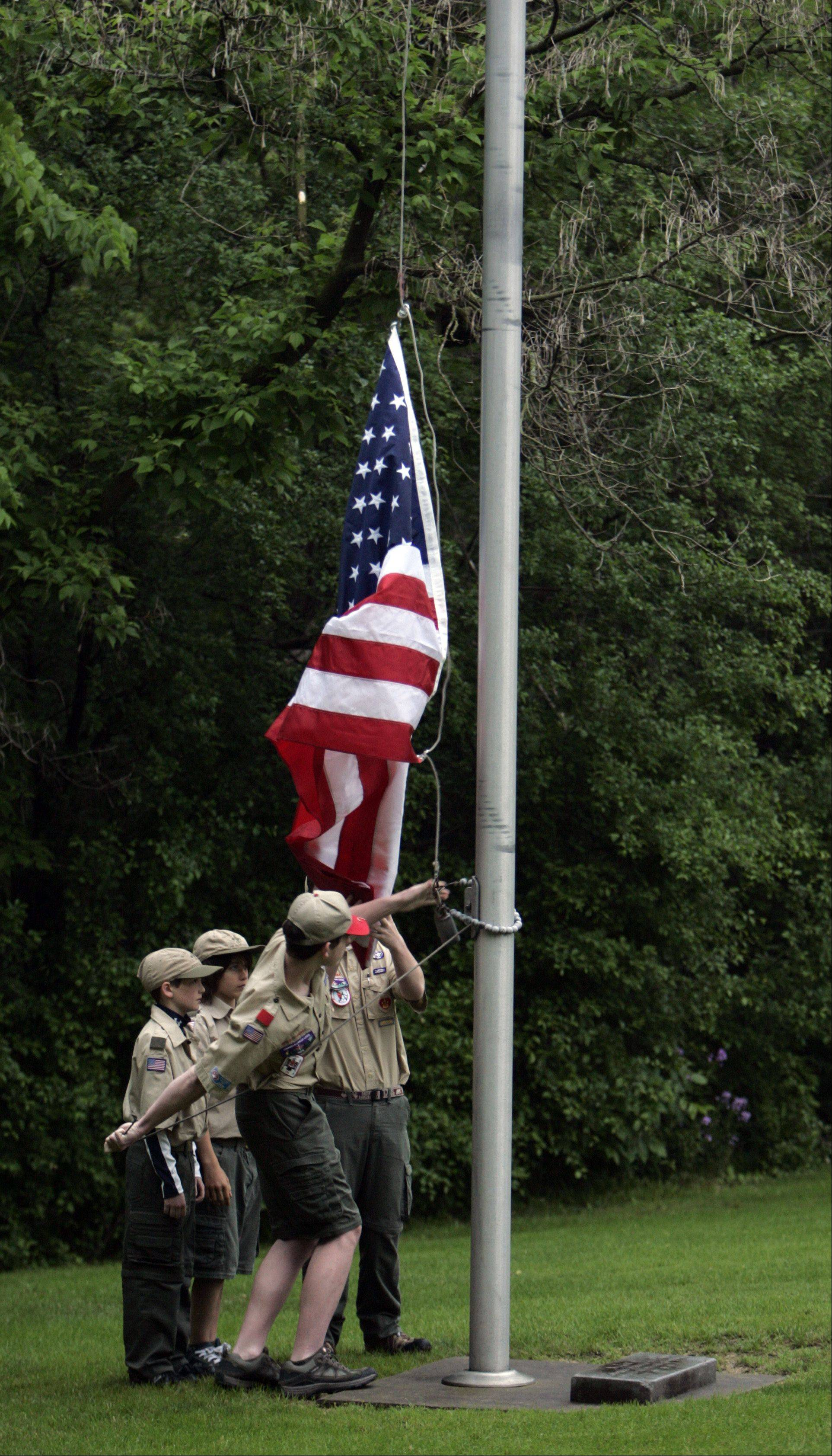 Members of Boy Scout Troop 46 raise the colors during the Memorial Day celebration at South Cemetery in St. Charles early Monday morning.