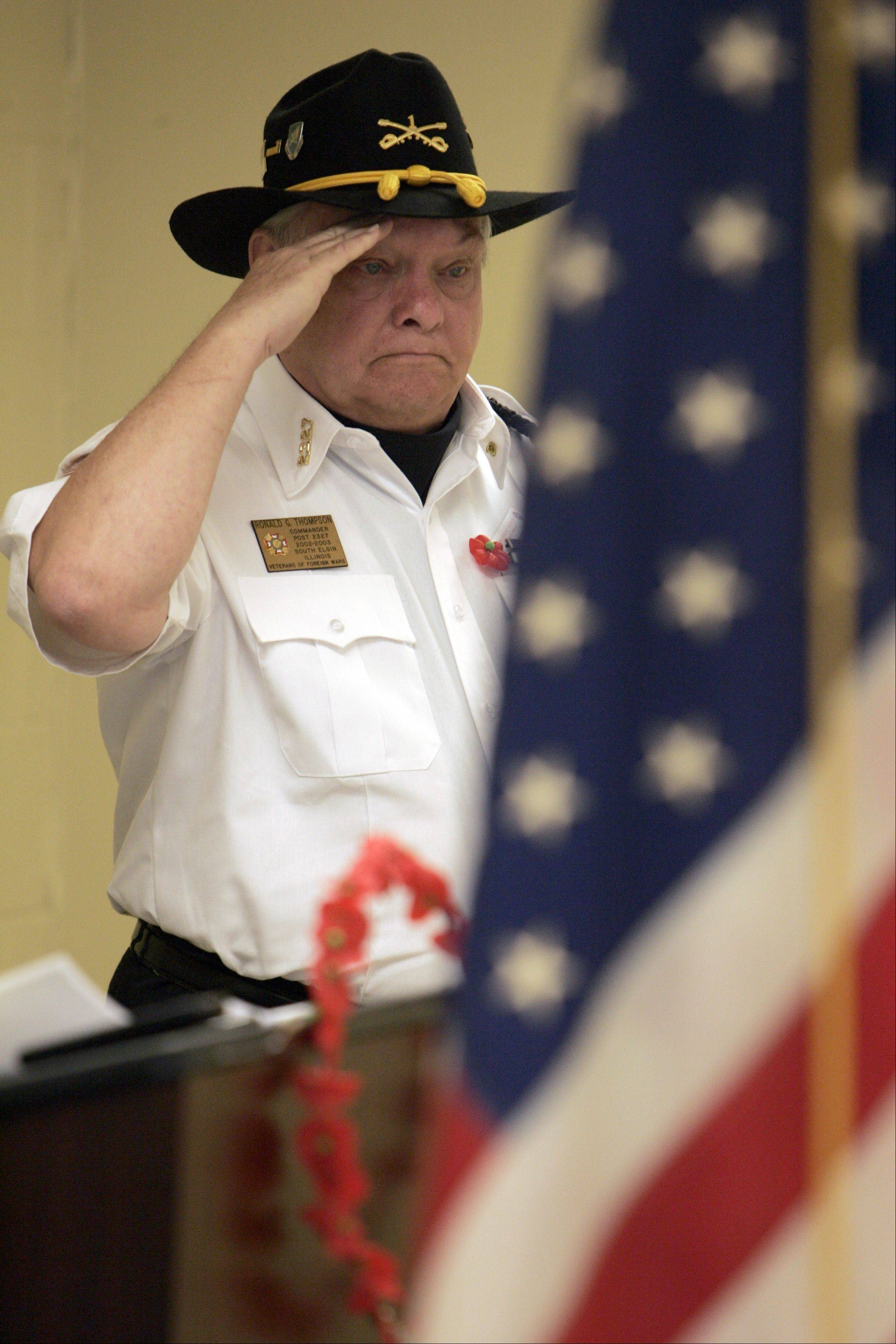 Ron Thompson who served with the First Calvary salutes the colors during the Memorial Day celebration in South Elgin Monday.