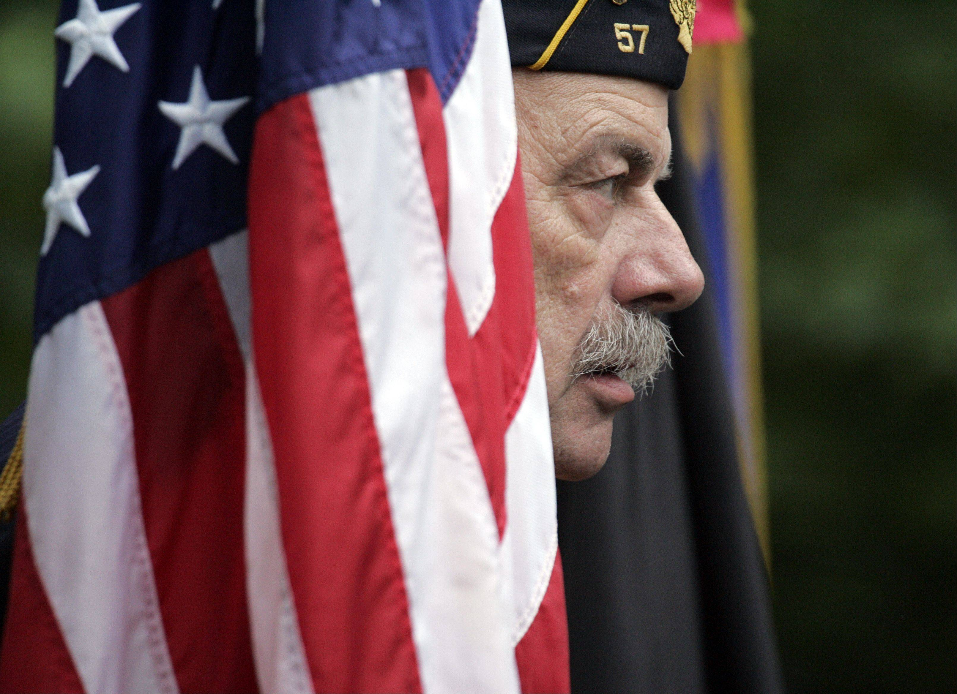 Rich Hamilton of American Legion Post 57 stands with the color guard during the Memorial Day celebration at Bluff City Cemetery in Elgin Monday. Hamilton of Elgin served in the Air Force.