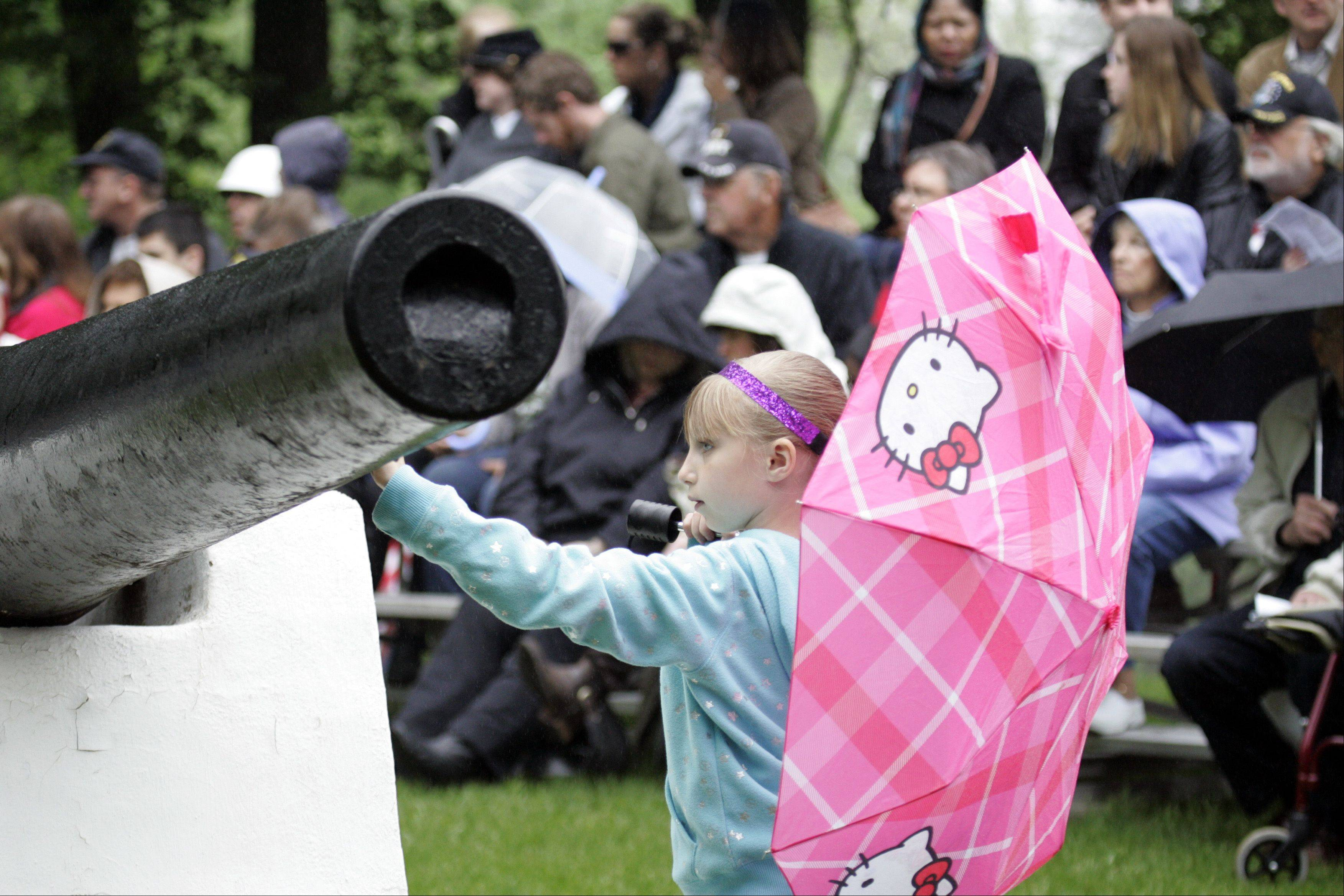 Seven-year-old Lynda Rotundo of Lake in the Hills gets a closer look at a canon before the Memorial Day celebration at Bluff City Cemetery in Elgin Monday.