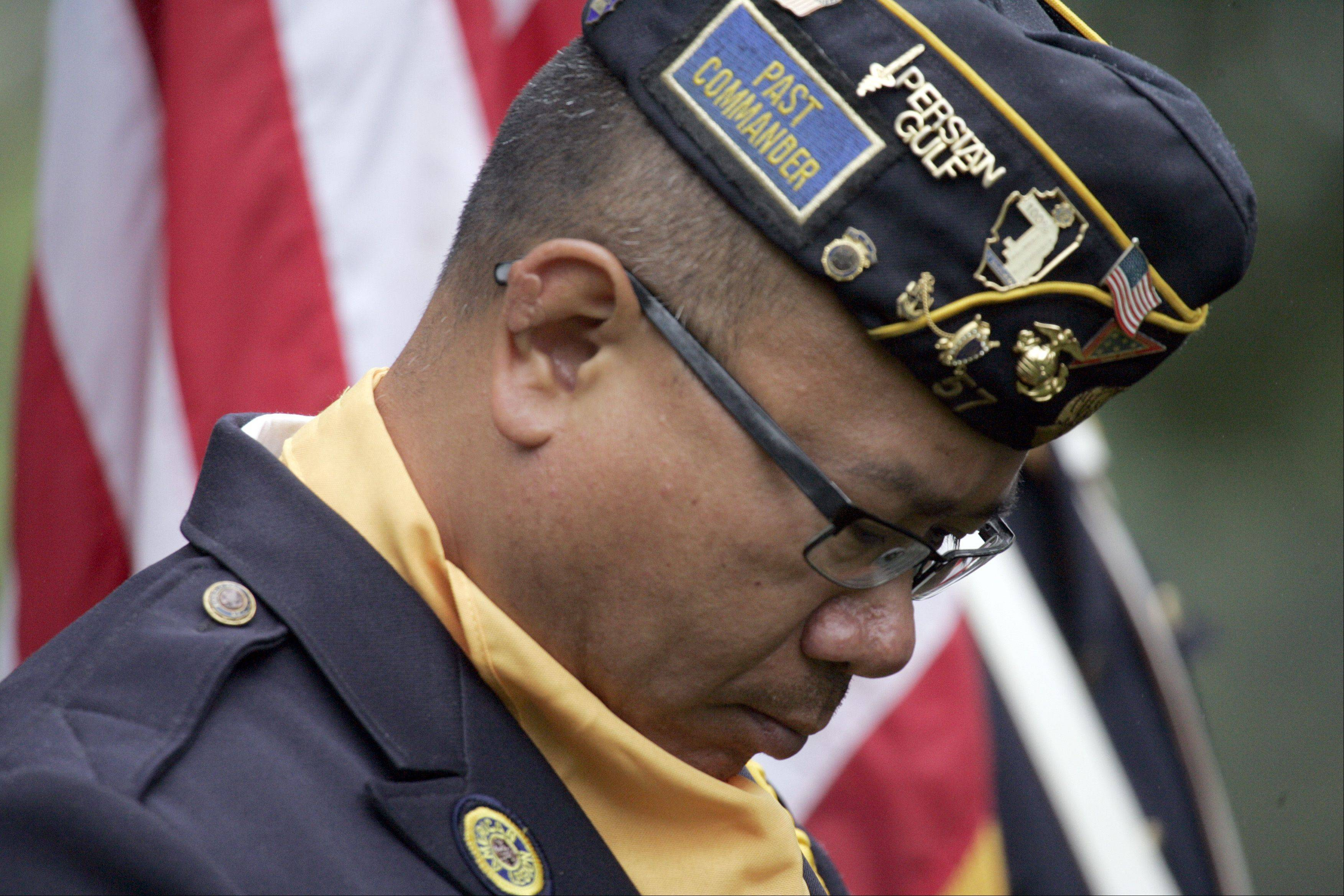 Pon Rattan of American Legion Post 57 takes a moment to reflect as names of the deceased are read during the Memorial Day celebration at Bluff City Cemetery in Elgin Monday. Rattan of Elgin served in the Marines.