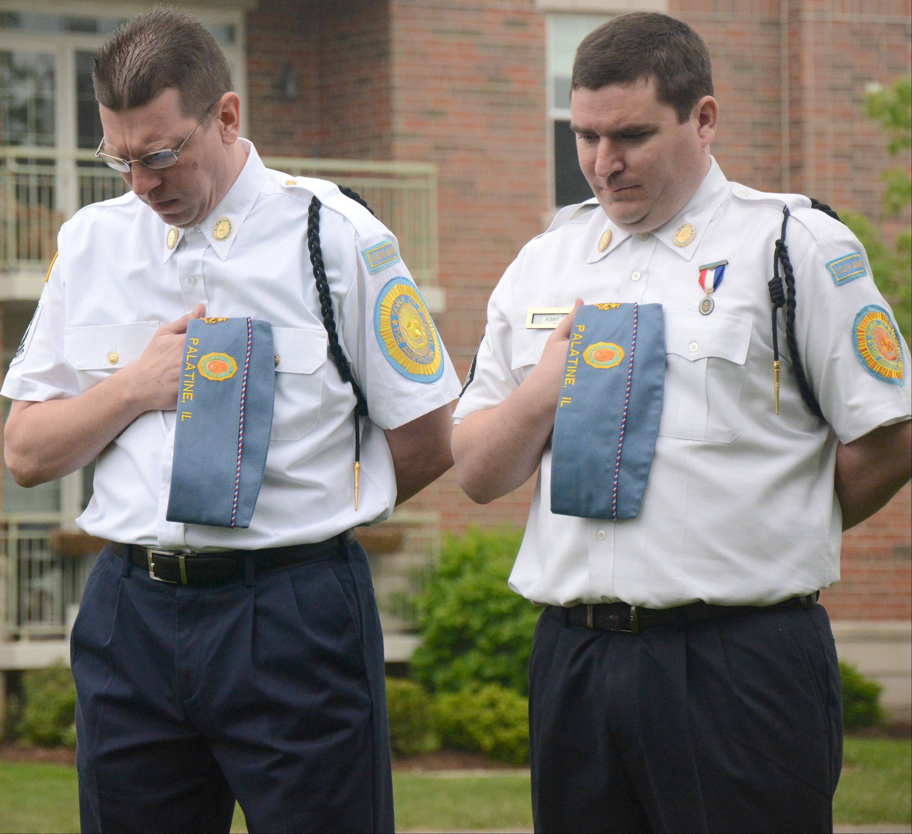 Sons of the American Legion Squadron 690 members Jason Foltyn, left, and Adam Anderson bow their heads during the invocation at the Palatine Memorial Day ceremony on Monday.