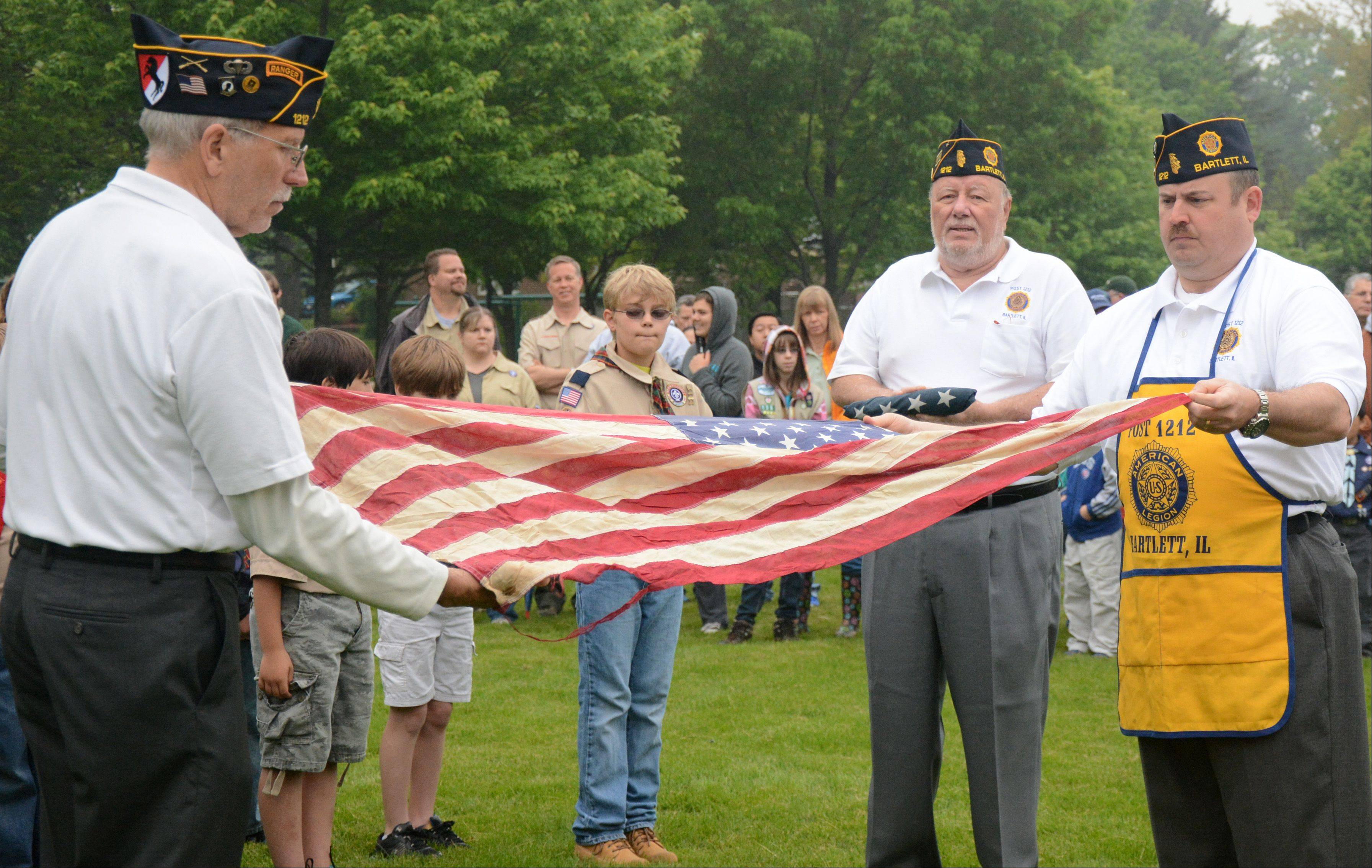 From left, VFW Post 1212 members Milt Lennert, Gene Ligocki and Derek Wright prepare a flag for burning during a flag retirement ceremony during the Bartlett Memorial Day ceremony on Monday.