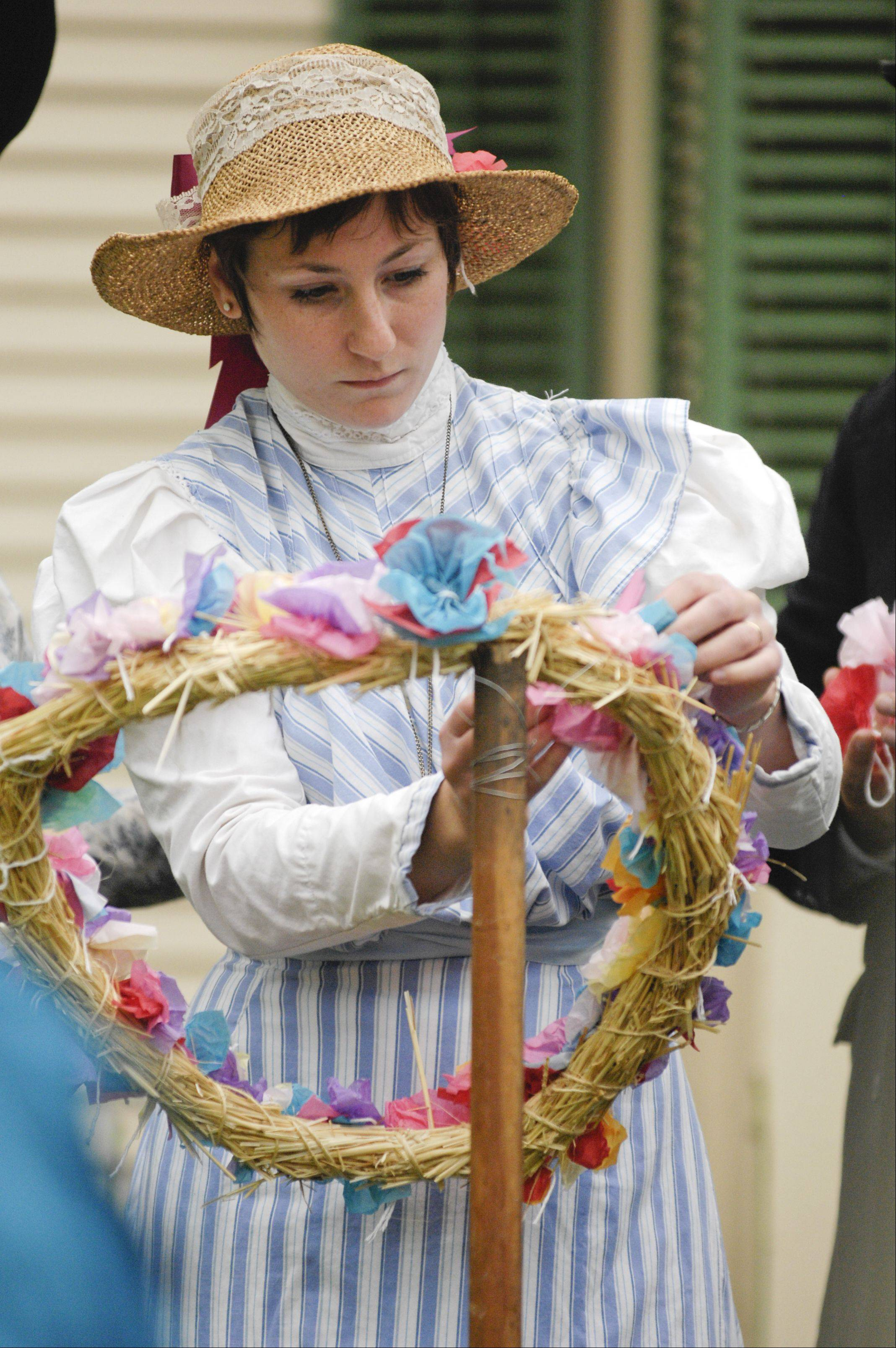 "Lindsay Rice of St. Charles adds paper flowers to a wreath in style of ""Decoration Day"" during a Memorial Day event Kline Creek Farm in West Chicago, Monday."