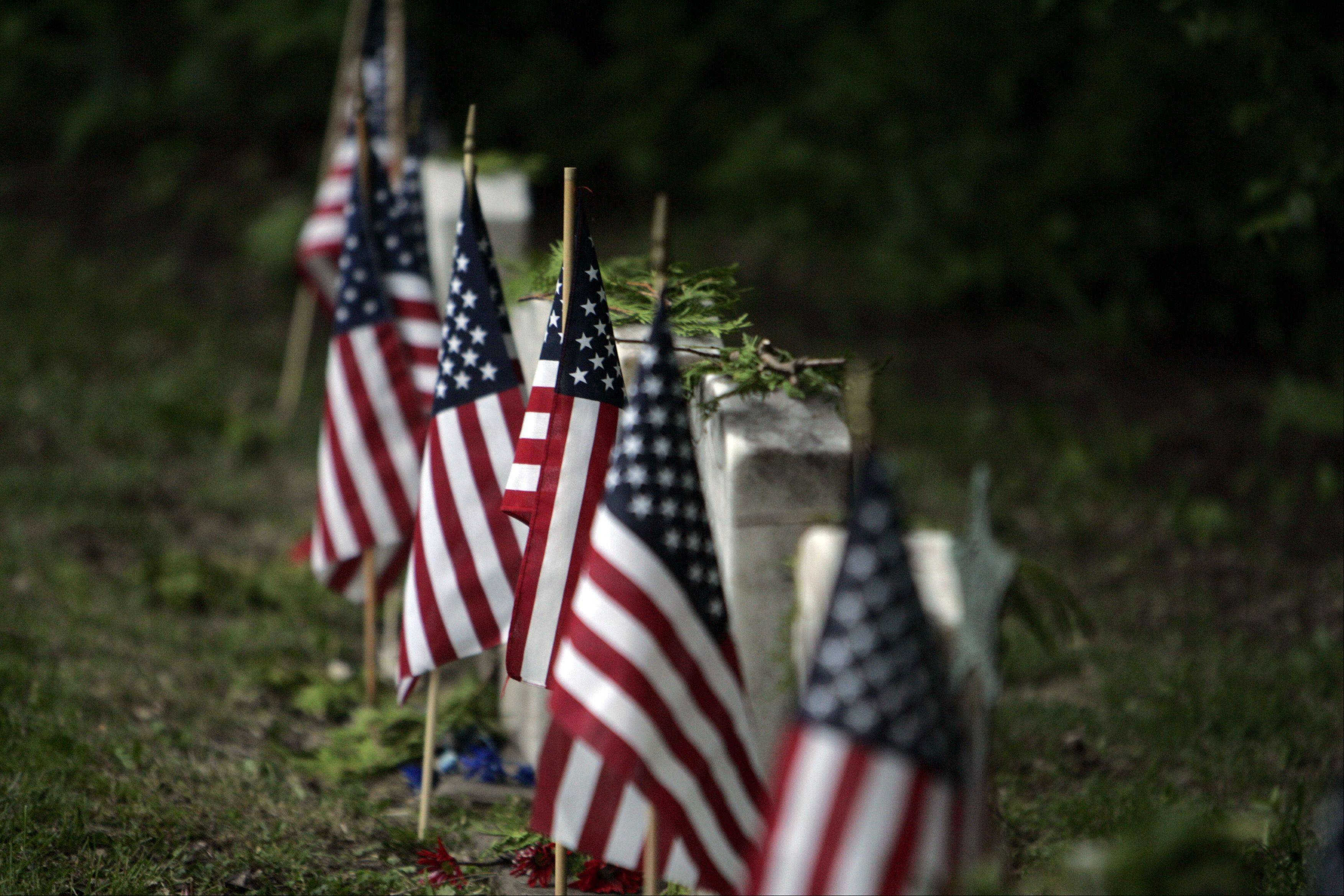 Flags sit along grave sites of past soldiers during the Memorial Day celebration at South Cemetery in St. Charles early Monday morning.