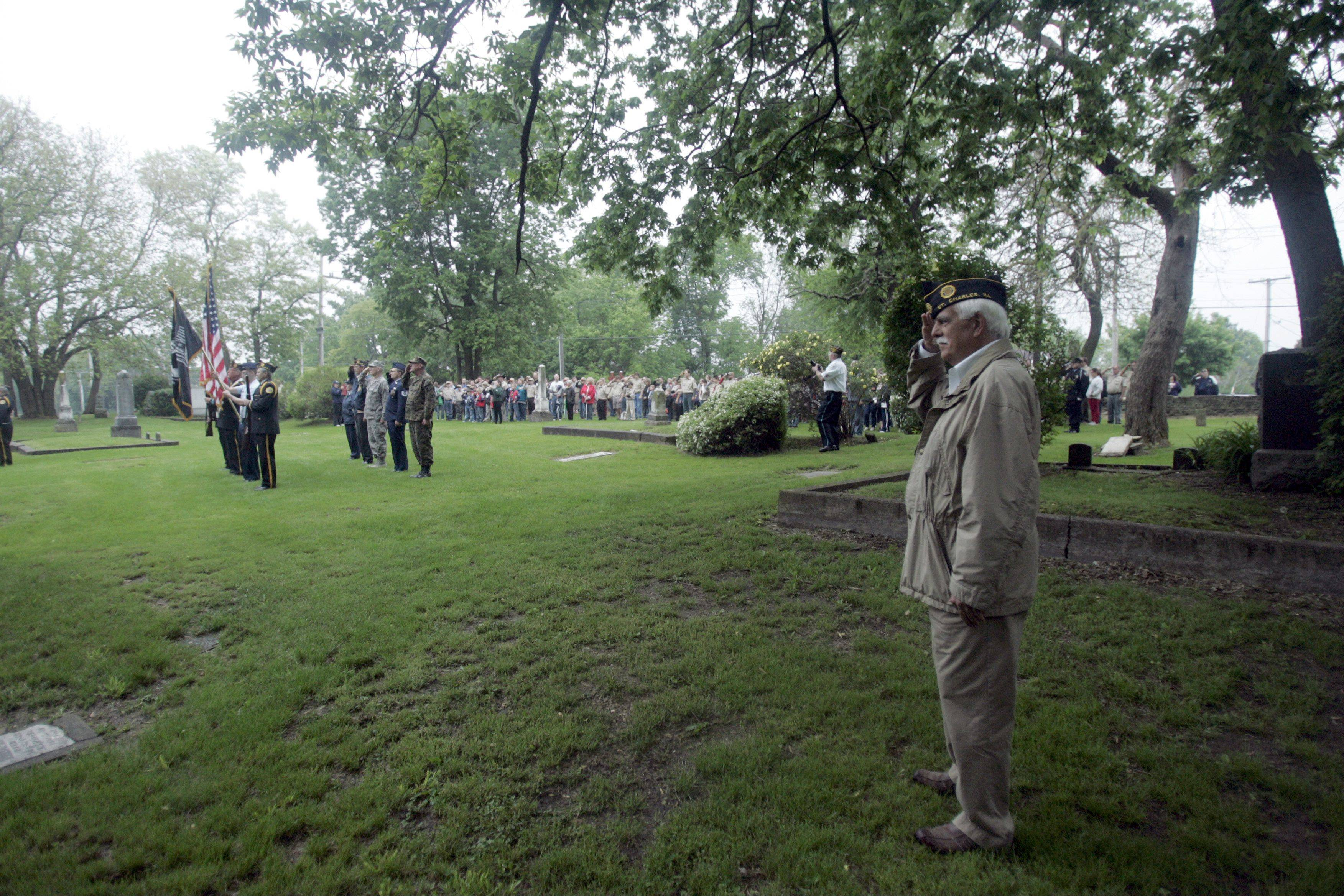 Ron Johnson of St. Charles and American Legion Post 342 stands at attention and salutes as the colors are presented during the Memorial Day celebration at South Cemetery in St. Charles early Monday morning.
