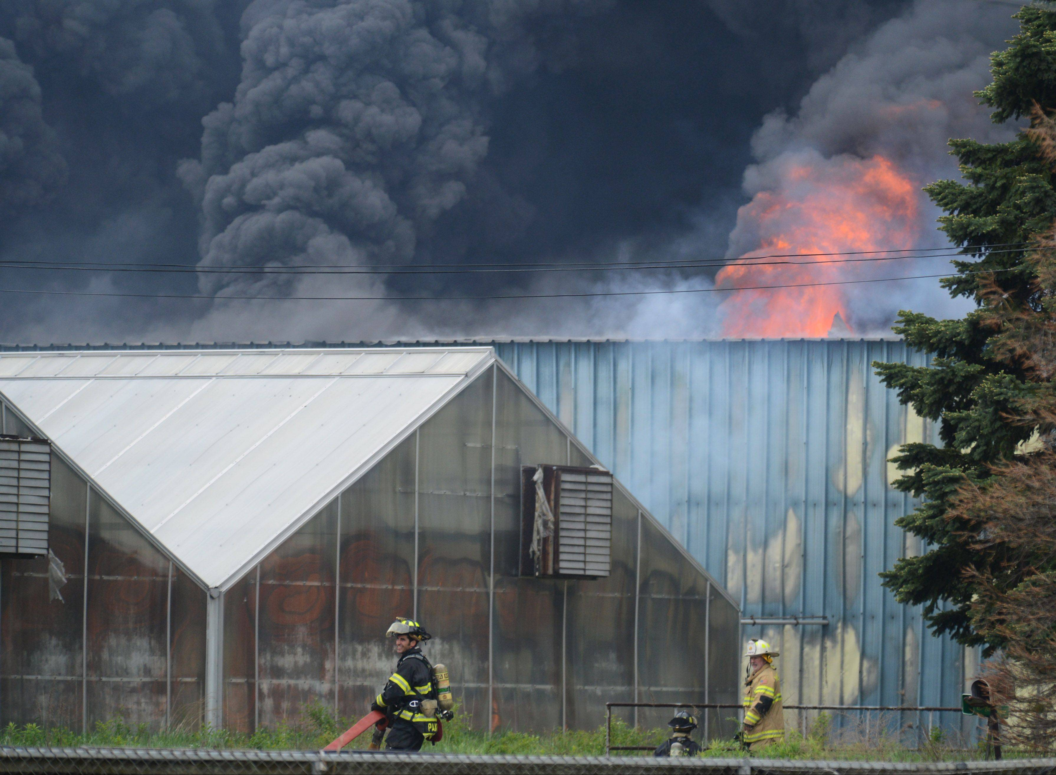 Heavy smoke and flames pour out of a structure at the former Jamaican Gardens nursery Monday on Route 176 in Libertyville.