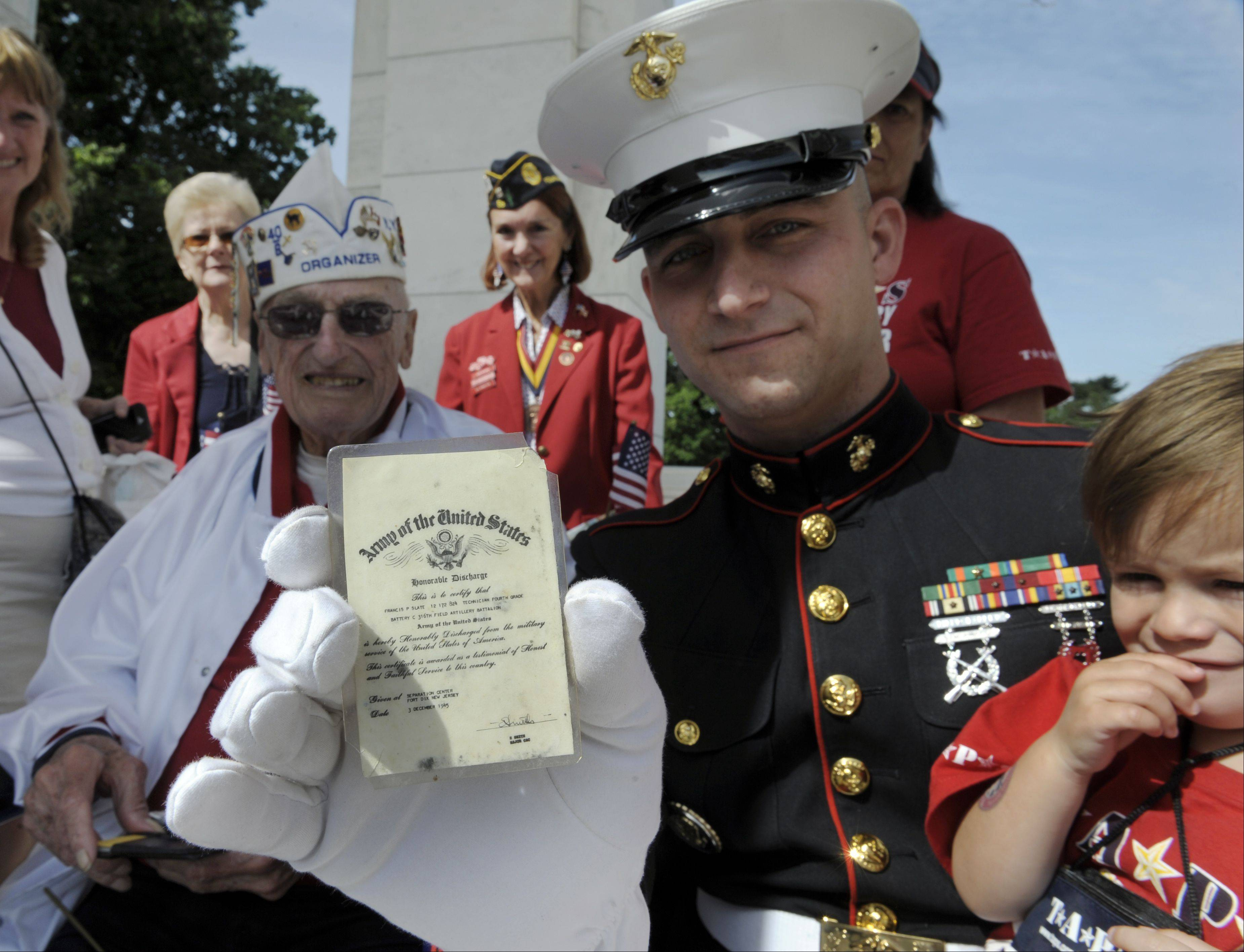 Marine Staff Sgt. Travis Hassell, center, and his son Issac show off Francis Slate's, left, Honorable Discharge Card from the U.S. Army Dec. 3, 1945, as they wait for President Barack Obama to deliver his Memorial Day address at Arlington National Cemetery in Arlington, Va., Monday, May 27, 2013.