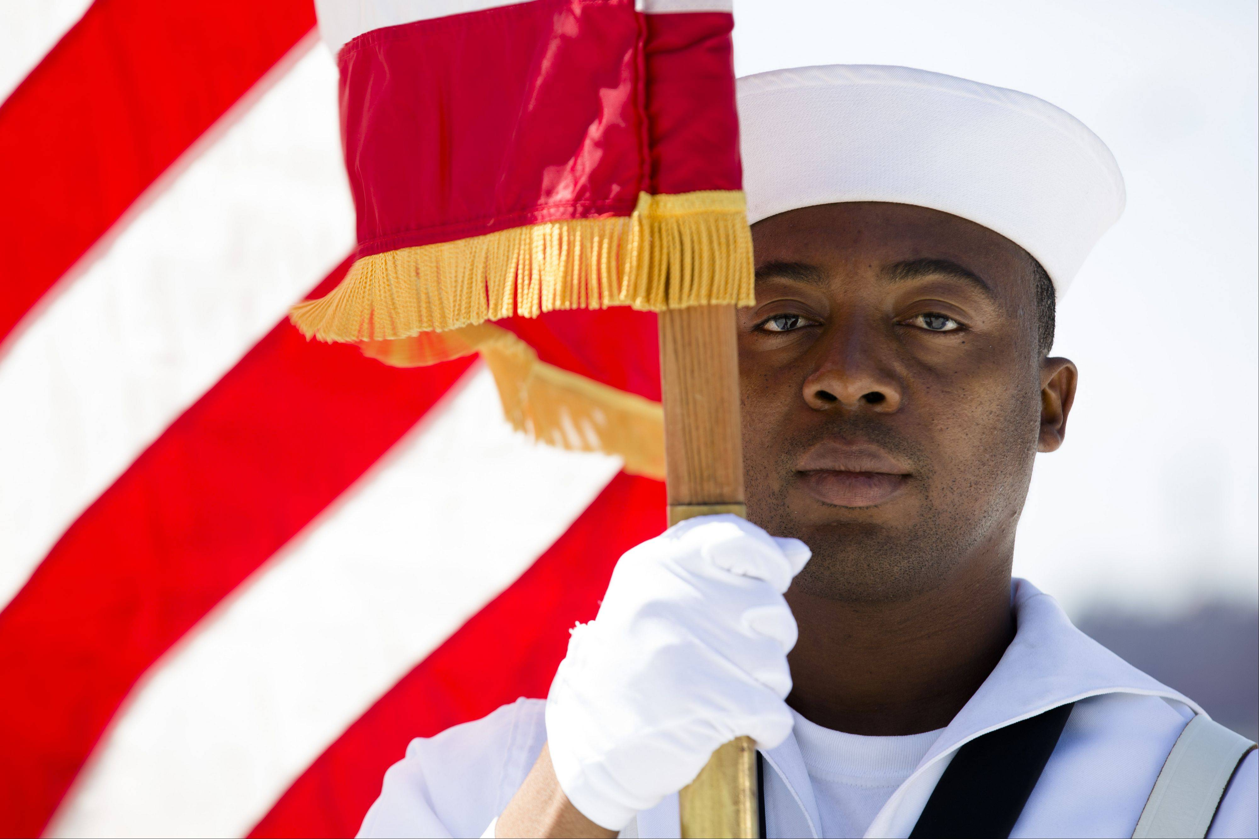 Seaman Daniel Odoi of the Navy Operational Support Center of New York City presents the American flag during a Memorial Day wreath laying at the Franklin D. Roosevelt Four Freedoms Park on Roosevelt Island, Monday, May 27, 2013, in New York.