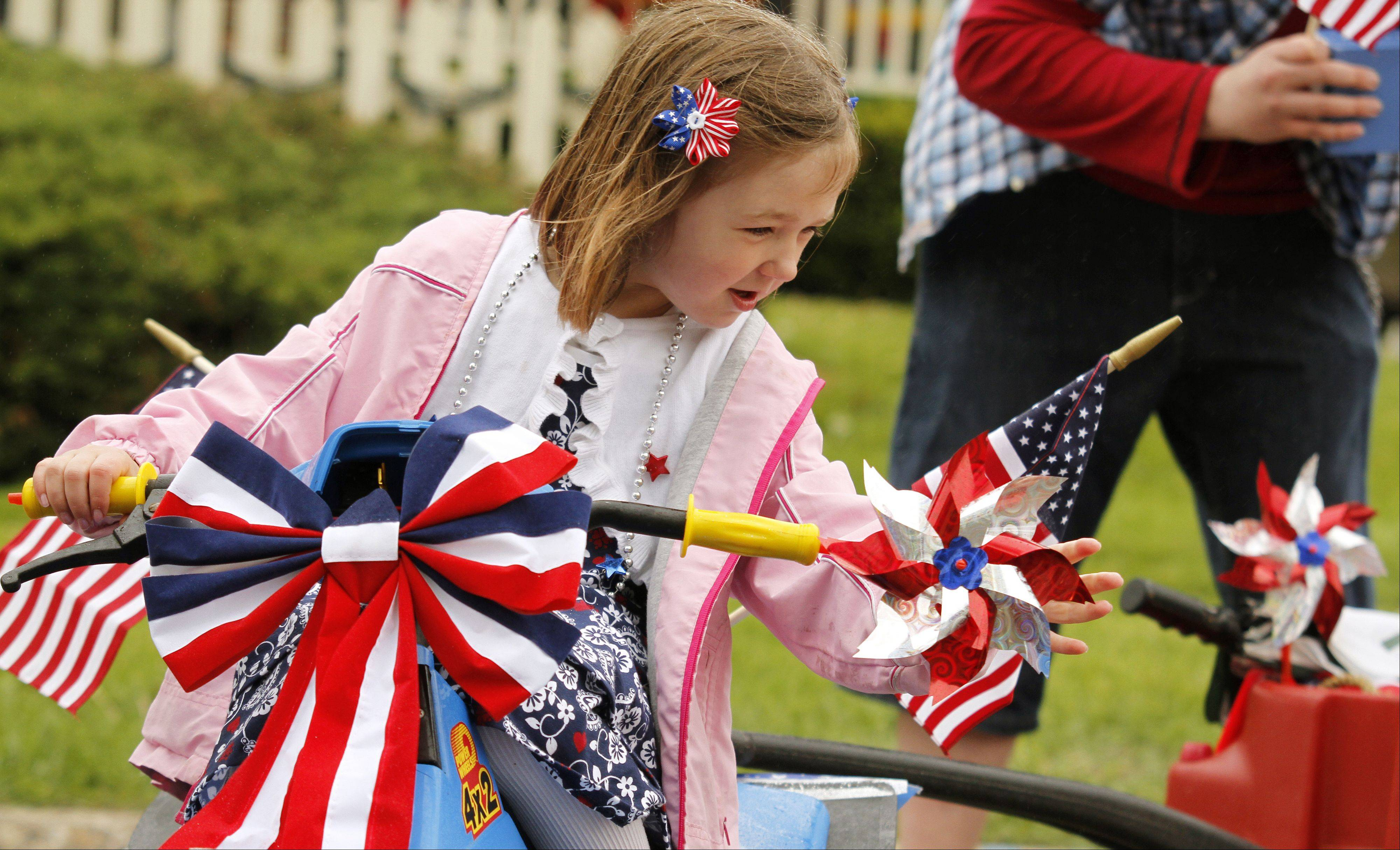 Relariel Webster, 6, of Hartford adjusts her pinwheels before the Memorial Day parade in West Bend on Monday, May 27, 2013.