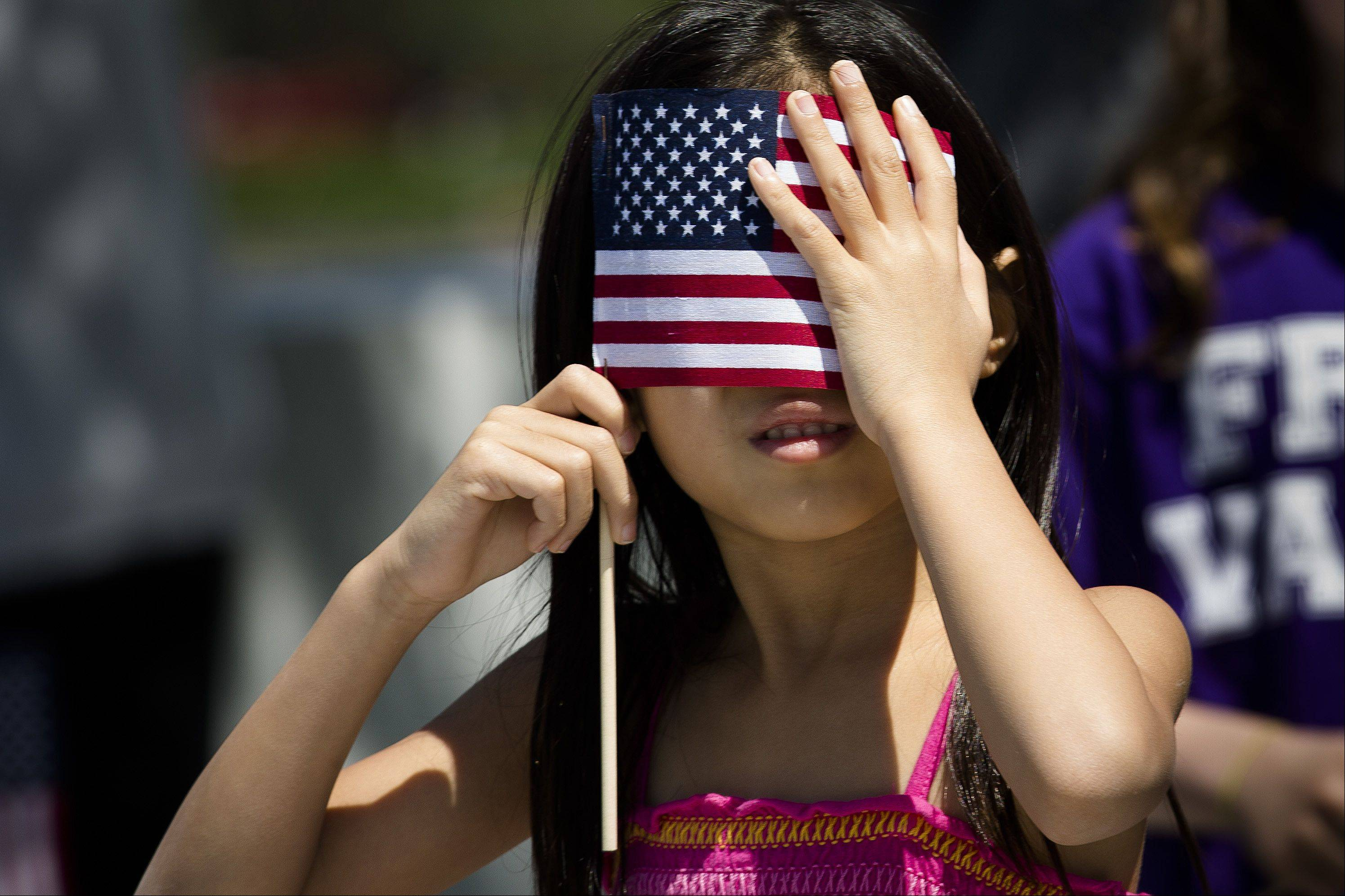 A young spectator shields her eyes from the sun with an American flag during a Memorial Day wreath laying at the Franklin D. Roosevelt Four Freedoms Park on Roosevelt Island, Monday, May 27, 2013, in New York.