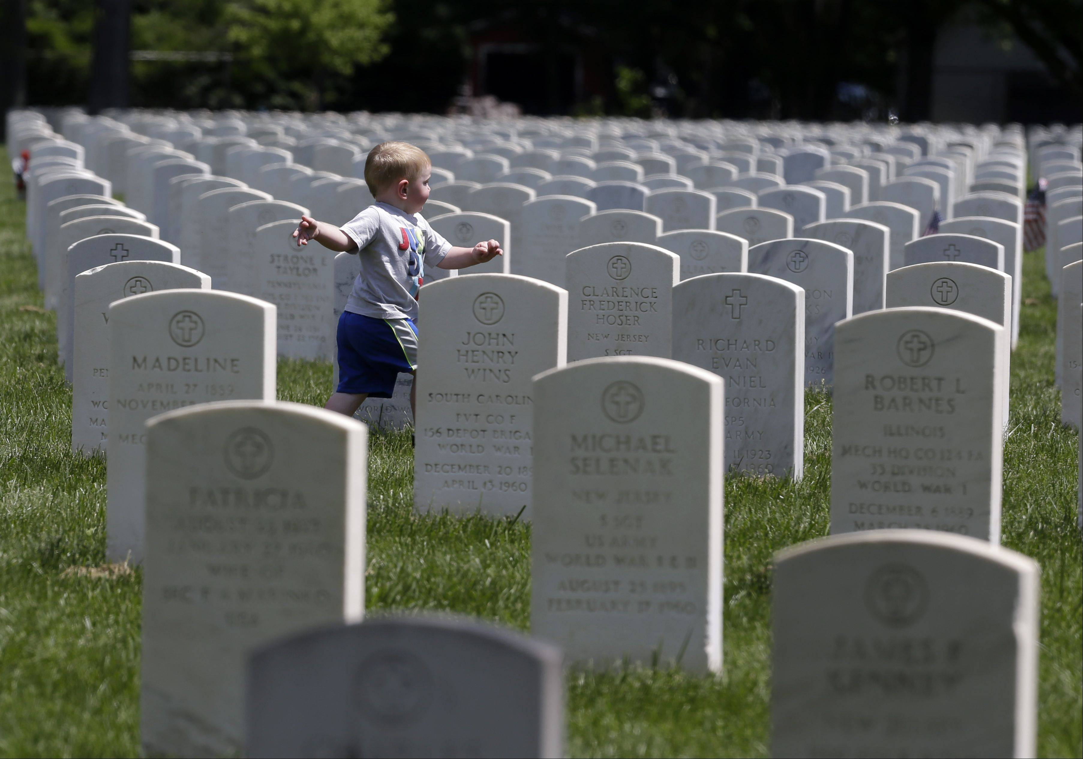 Matthew McGinley, 2, of Philadelphia, Pa., runs on at the Beverly National Cemetery in Beverly, N.J., on Memorial Day, Monday, May 27, 2013, as his family visits the gravesite of his great-grandfather, a World War I veteran.