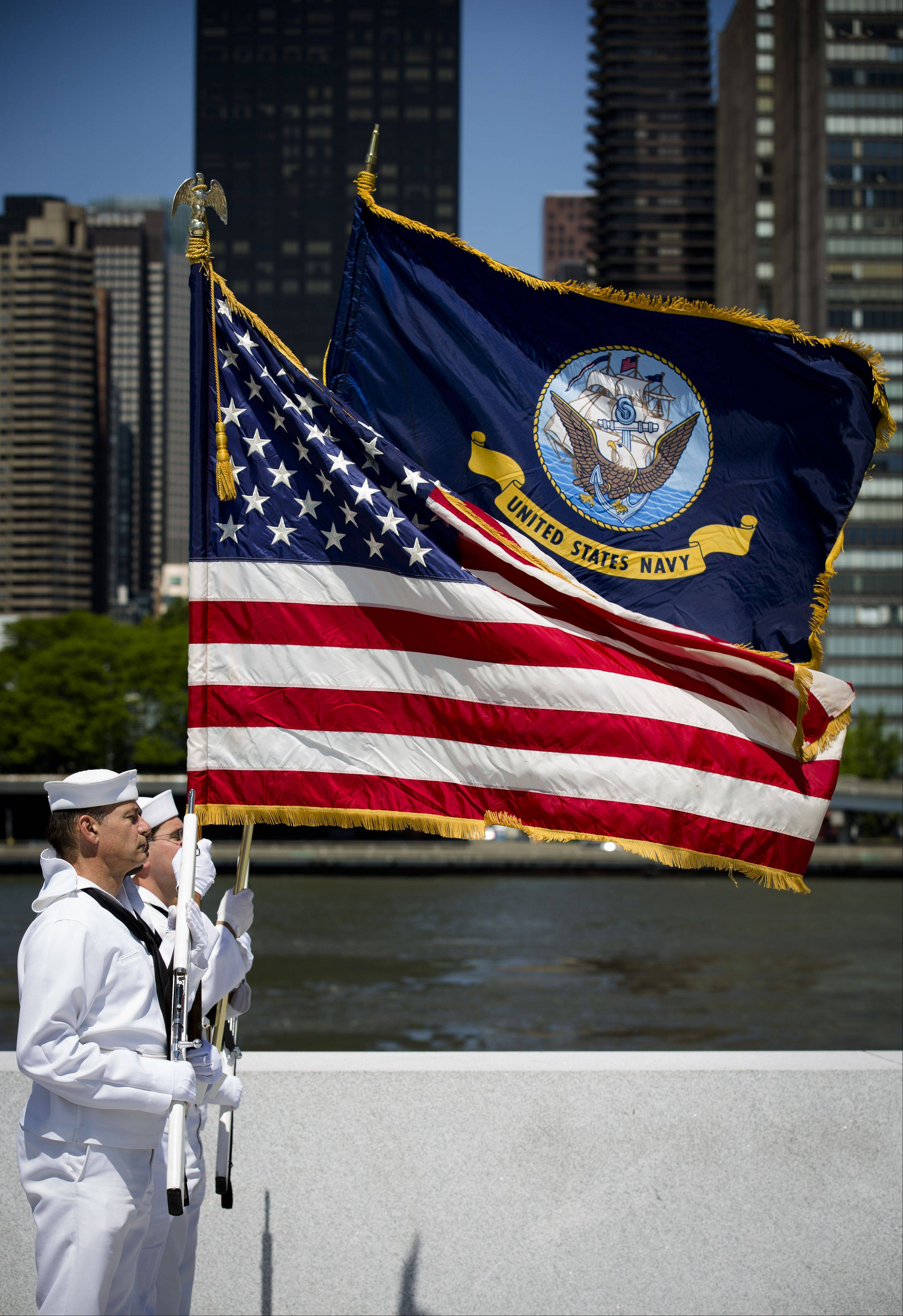 Seamen from the Navy Operational Support Center of New York City present flags during a Memorial Day wreath laying at the Franklin D. Roosevelt Four Freedoms Park on Roosevelt Island, Monday, May 27, 2013, in New York.