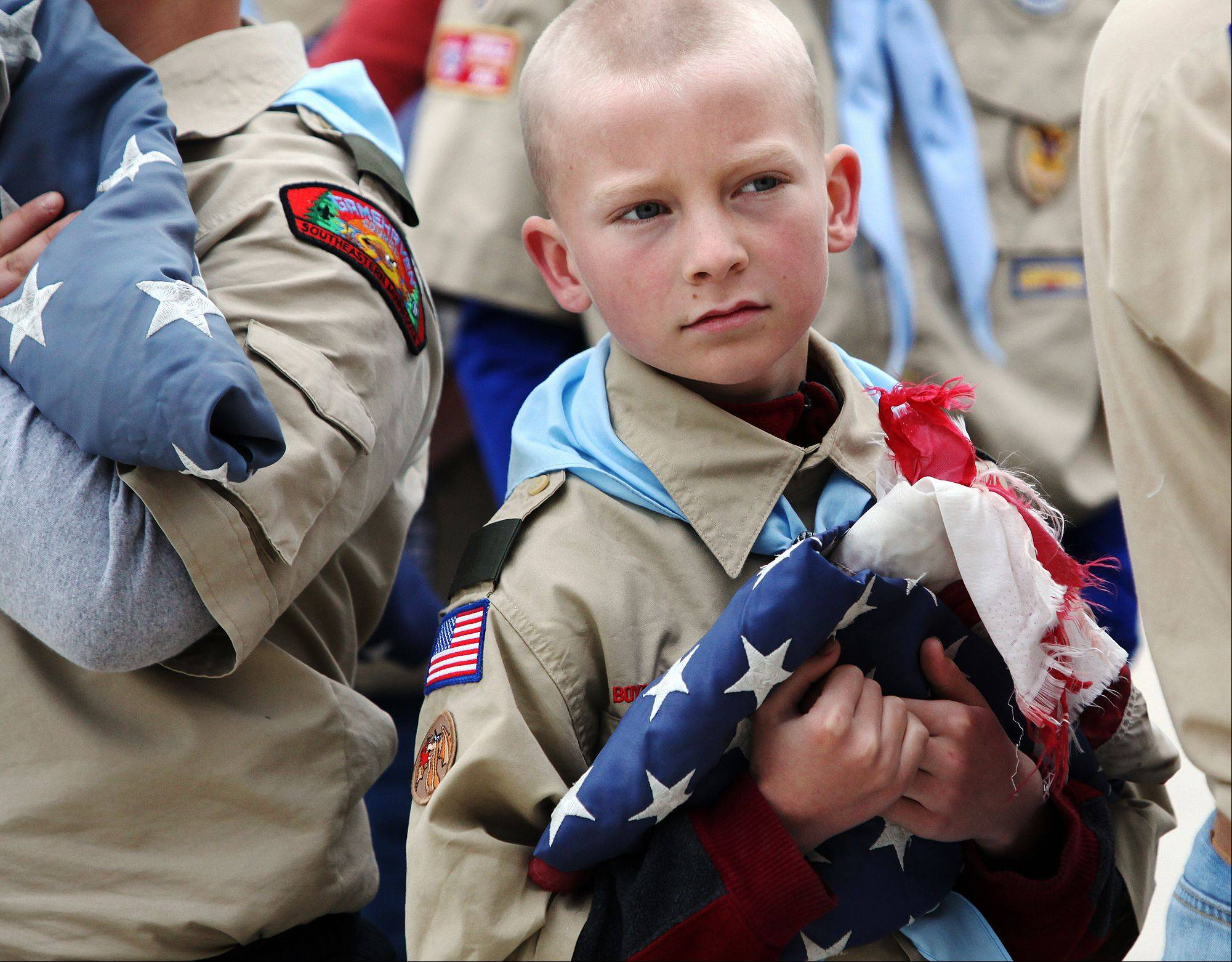 Jeremy Rivers of Boy Scout Troop 13 from St. Mary's Catholic Church holds a tattered American flag Monday, May 27, 2013, during a Memorial Day flag retirement ceremony at Sugarloaf Assisted Living in Winona, Minn. The troop retired nine American flags from the community by burning them in a ceremonial fire and later burying the ashes.