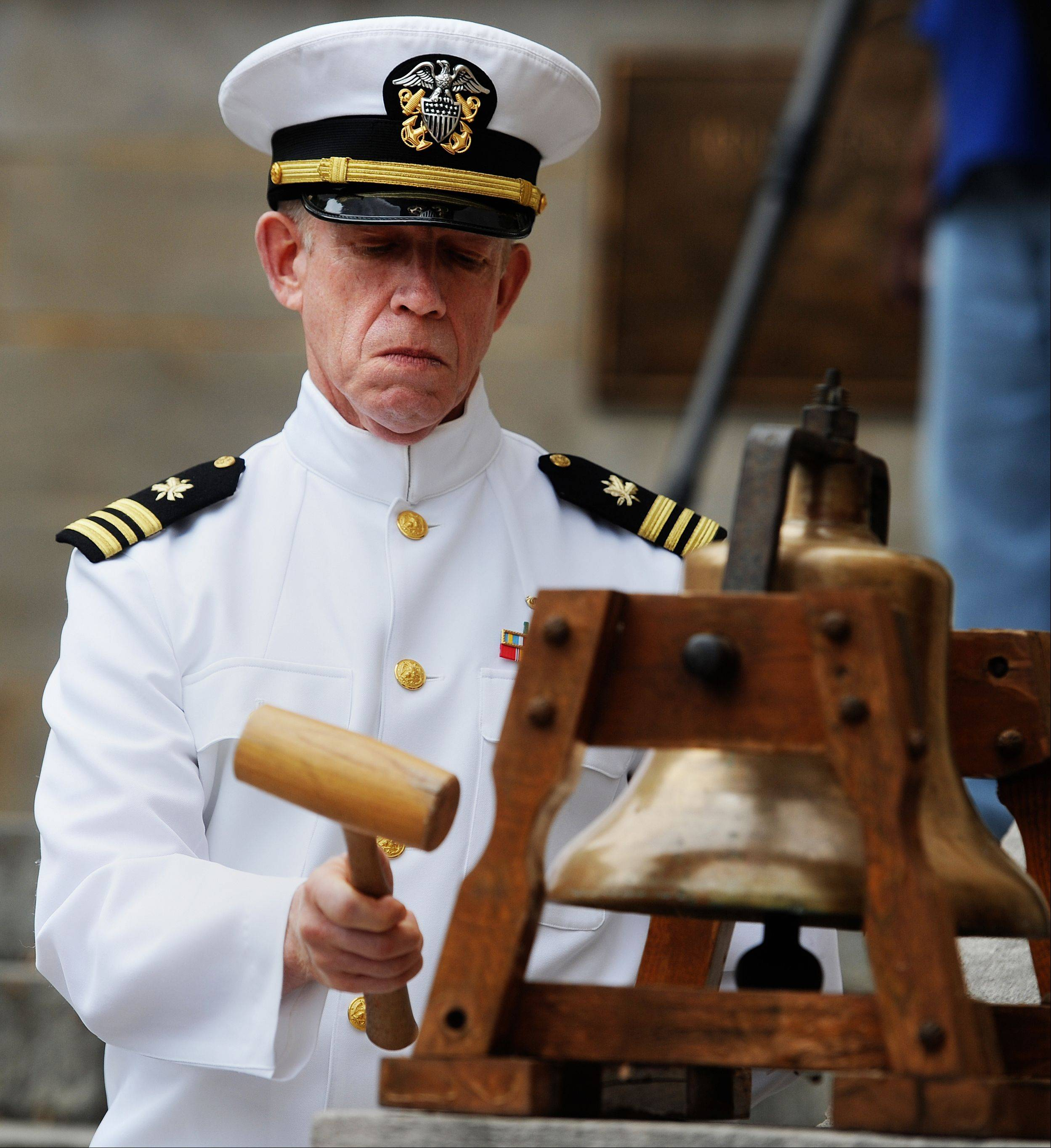 U.S. Navy veteran Paul Webb strikes the bell throughout the Memorial Day service, in Lynchburg, VA., Monday, May 27, 2013.