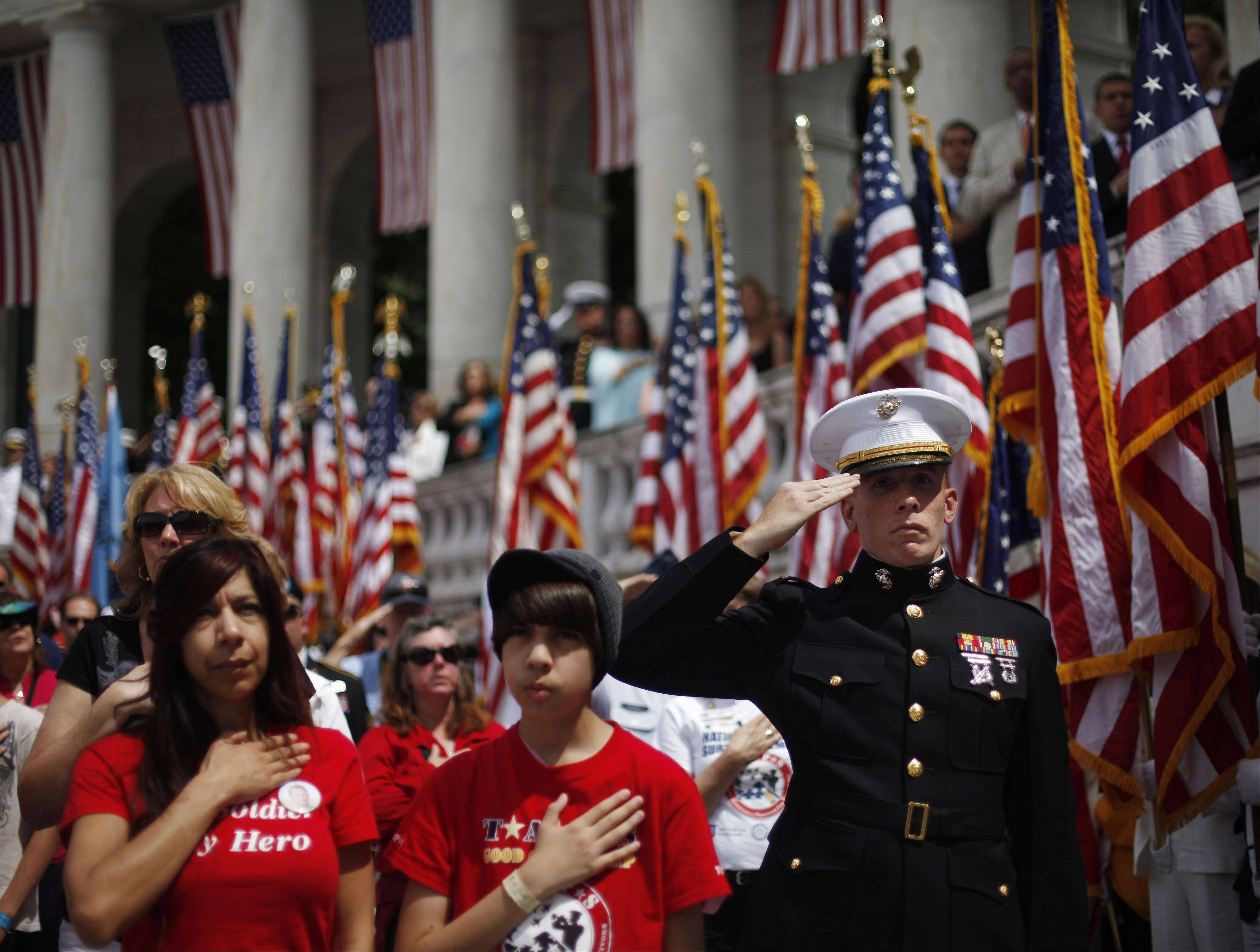 U.S. Marine Corps, 2nd Lt. Adam Carroll, right, with Maria Thomas, left, and Craig Thomas, center, salute and hold hands to their hearts during the playing of the national anthem at the Memorial Day Observance in the Memorial Amphitheater at Arlington National Cemetery, May 27, 2013, in Arlington, Va.