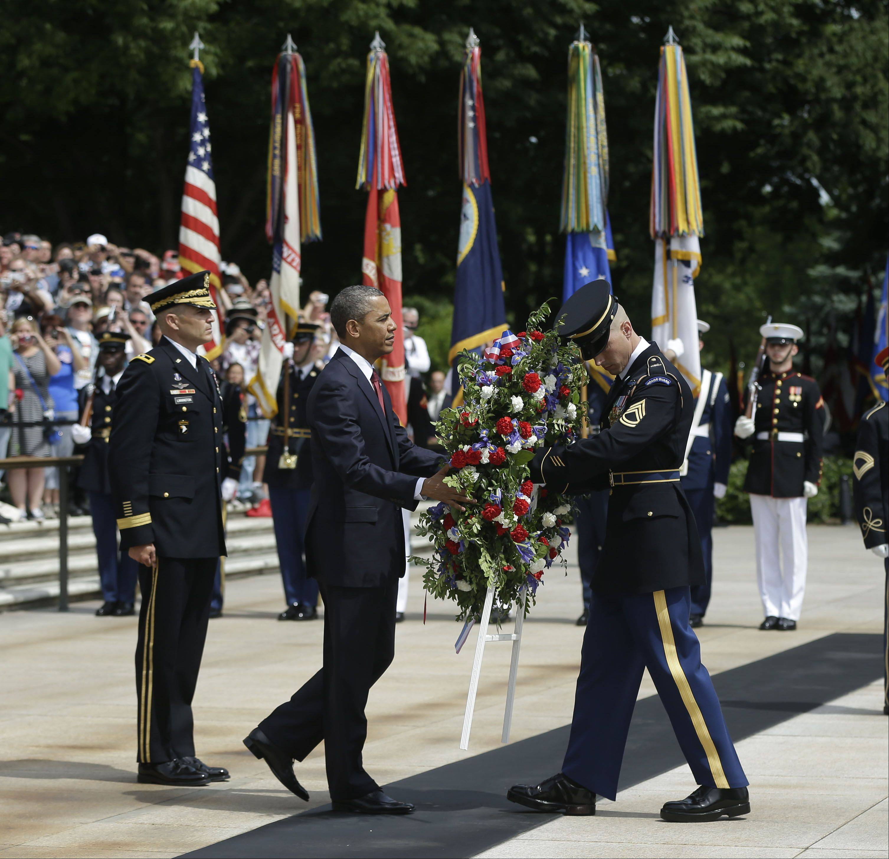 President Barack Obama, center, participates in the wreathlaying ceremony at the Tomb of the Unknowns with Maj. Gen. Michael S. Linnington, left, Commander of the U.S. Army Military District of Washington, at Arlington National Cemetery on Memorial Day, May 27, 2013, in Arlington, Va.