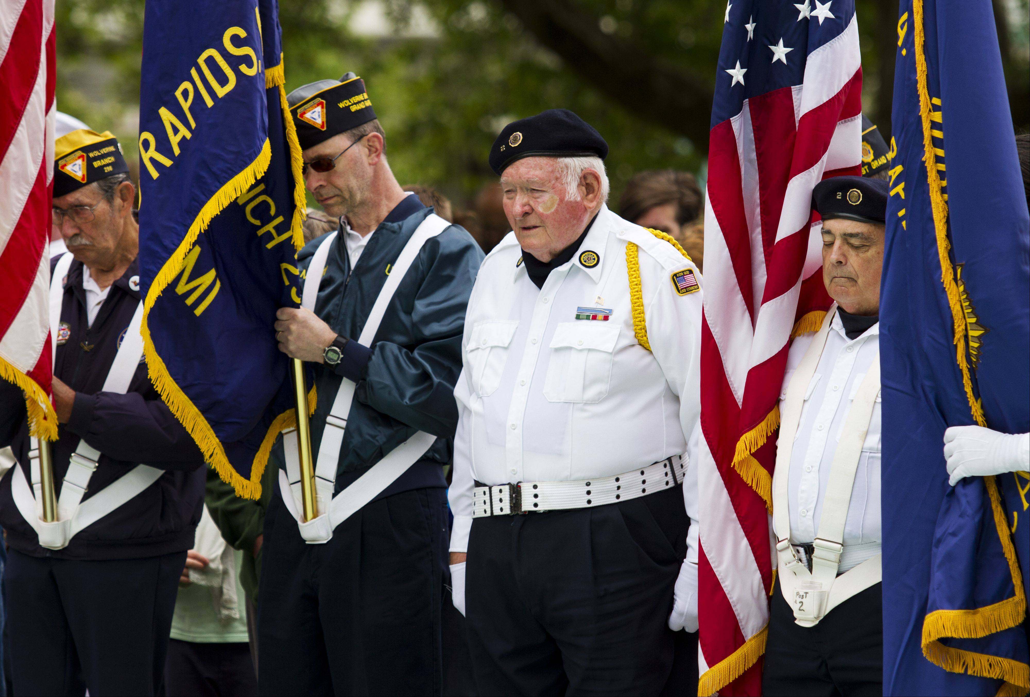From left, Bob Coukendall, Marty Posekany from the Fleet Reserve Association and American Legion Post 2 members Bill Brinkman and Scott Harvey attend a Memorial Day ceremony at Veterans Memorial Park Monday, May 27, 2013 in Grand Rapids Mich.