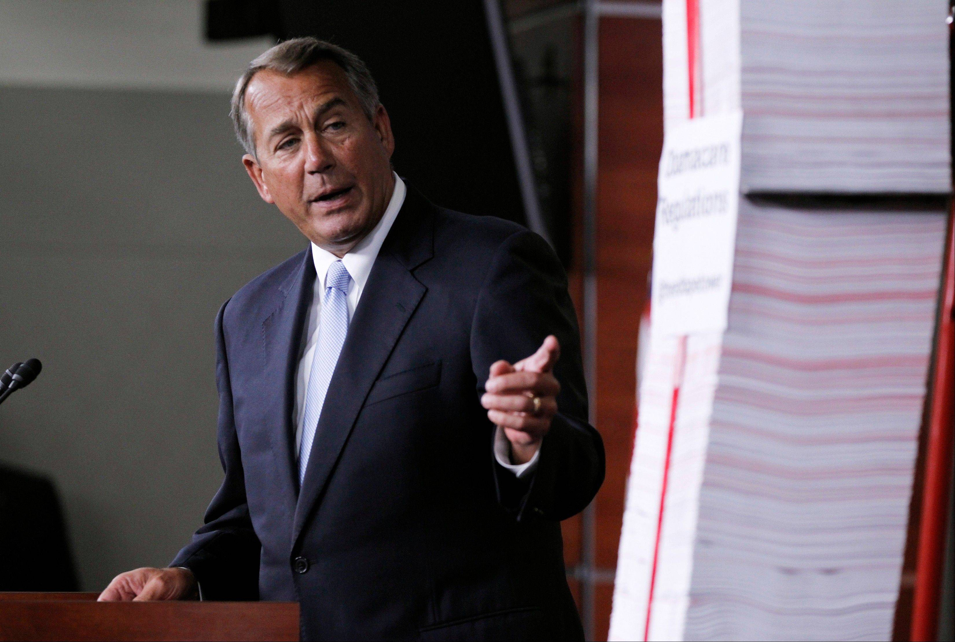 House Speaker, Republican John Boehner of Ohio, points toward the tall stack of paper, representing 20,000 pages of Affordable Care Act regulations, during a news conference on Capitol Hill in Washington.