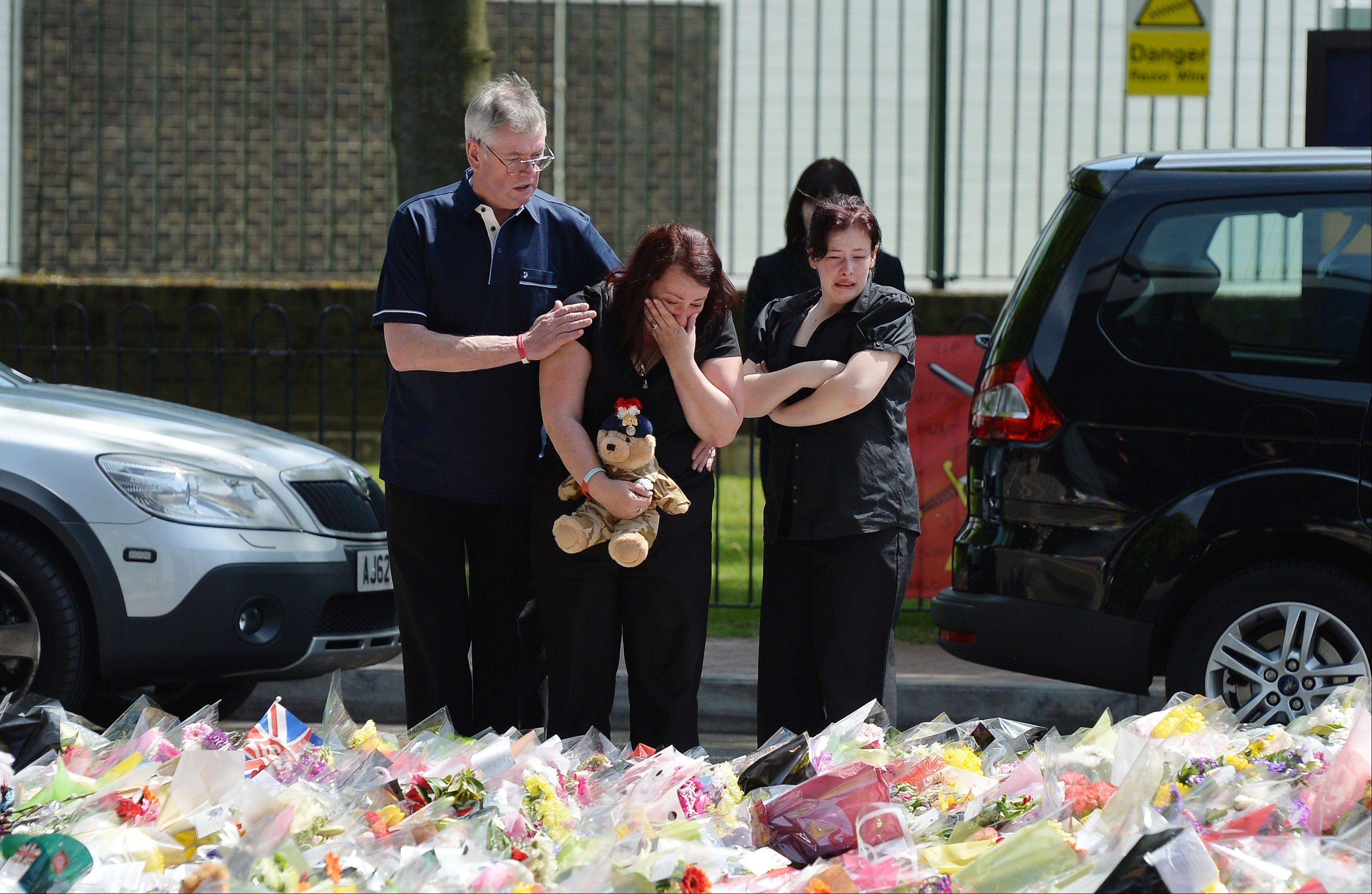 Lyn Rigby, mother of Drummer Lee Rigby, holding a teddy bear joins other family members as they look at floral tributes outside Woolwich Barracks left by well wishers as they visited the scene of the 25-year-old soldier's murder in Woolwich, south-east London, Sunday May 26, 2013.