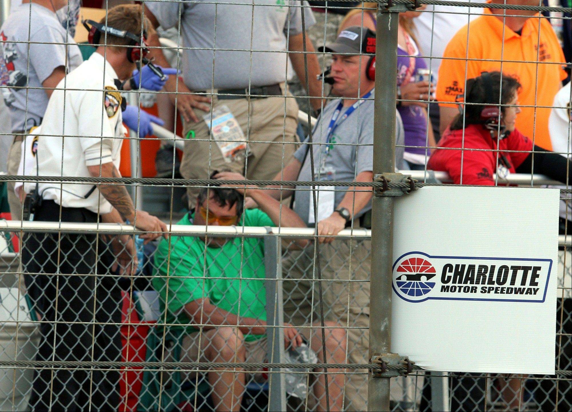In this photo provided by Fernando Echeverria, security personnel assist a fan injured by a broken television camera cable during the NASCAR Sprint Cup series Coca-Cola 600 auto race at Charlotte Motor Speedway in Concord, N.C., Sunday, May 26, 2013.