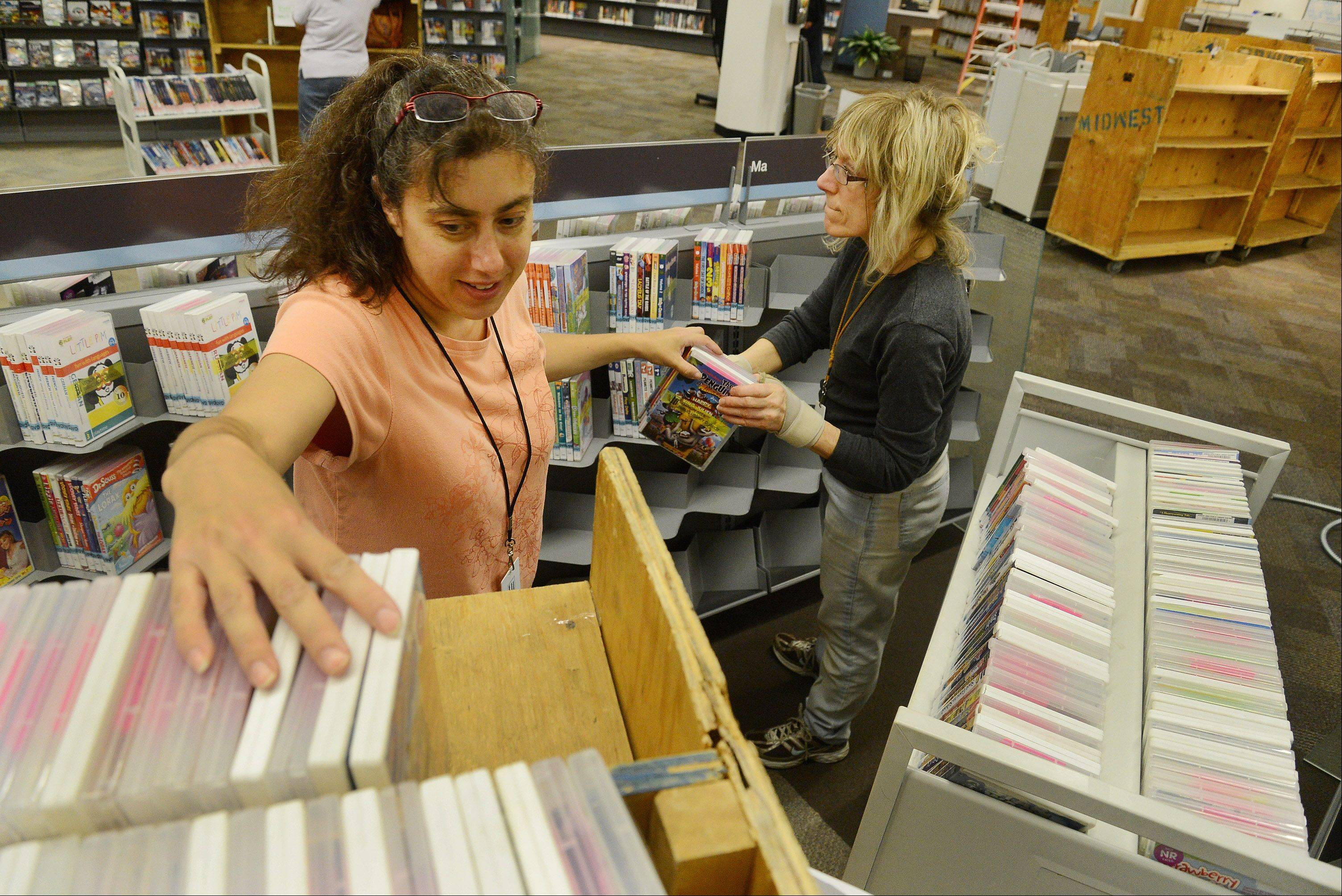 Circulation staff members Donna Wallach, left, and Teri Dobrow stack DVDs on shelves in the newly renovated Vernon Area Library. Roughly 20,000 items needed to be moved in after a $1.3 million renovation.