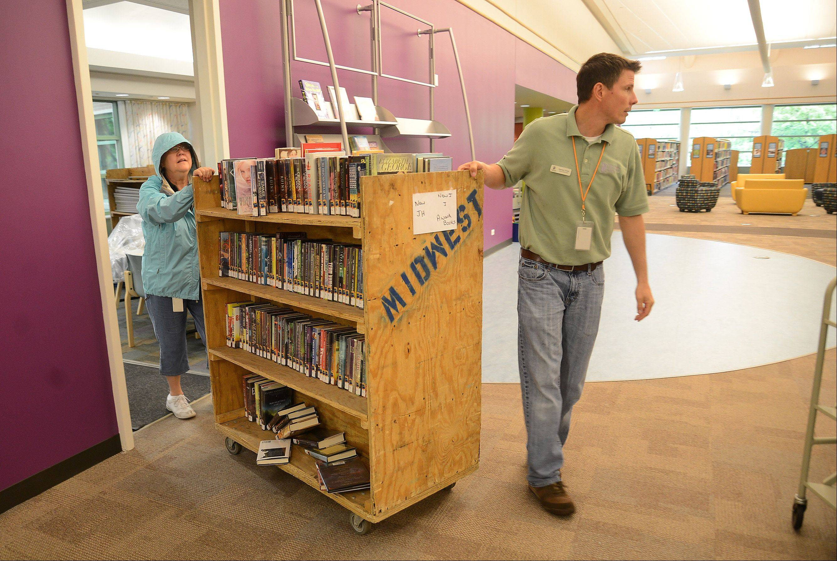 Head of Circulation Stephen Territo and Circulation Coordinator Vivien Starr move a cart full of books and DVDs from the library annex back to the newly renovated Vernon Area Library.