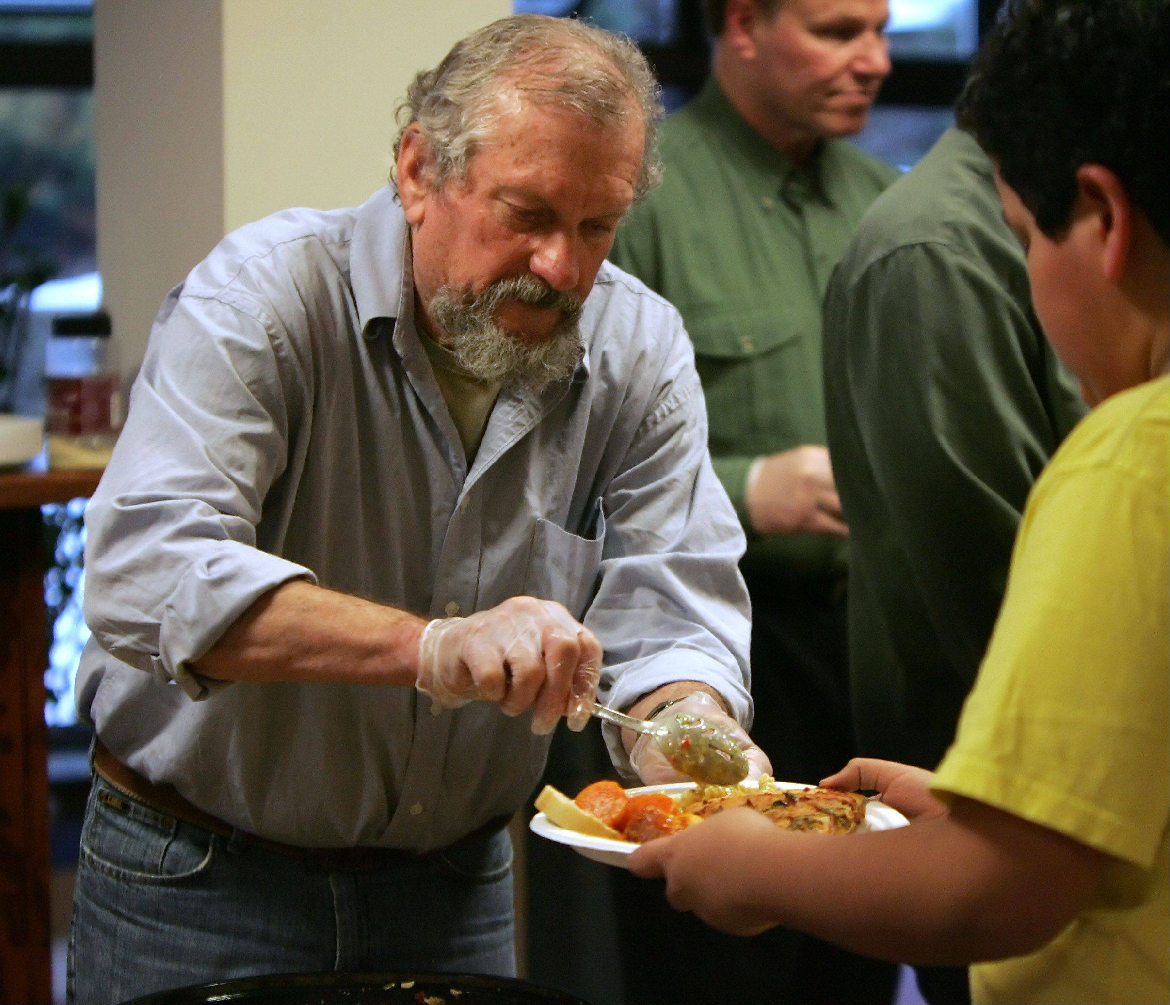 Volunteer Al Ceisel, of Crystal Lake, dishes out food to guests served by Emmaus House of Hospitality, a Lake County charity, at St. Francis de Sales Catholic Church in Lake Zurich. Each Sunday, financially stretched families are given a good meal and provided groceries from the food pantry to take home.