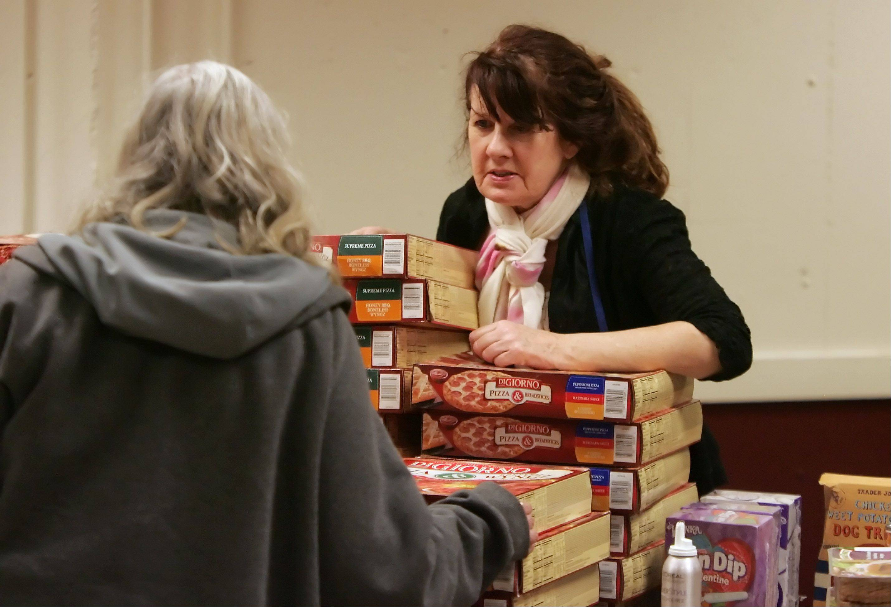 Volunteer Kathleen Murray, of Hawthorn Woods, helps a guest in the food pantry as groceries are given out by Emmaus House of Hospitality, a Lake County charity, at St. Francis de Sales Catholic Church in Lake Zurich.