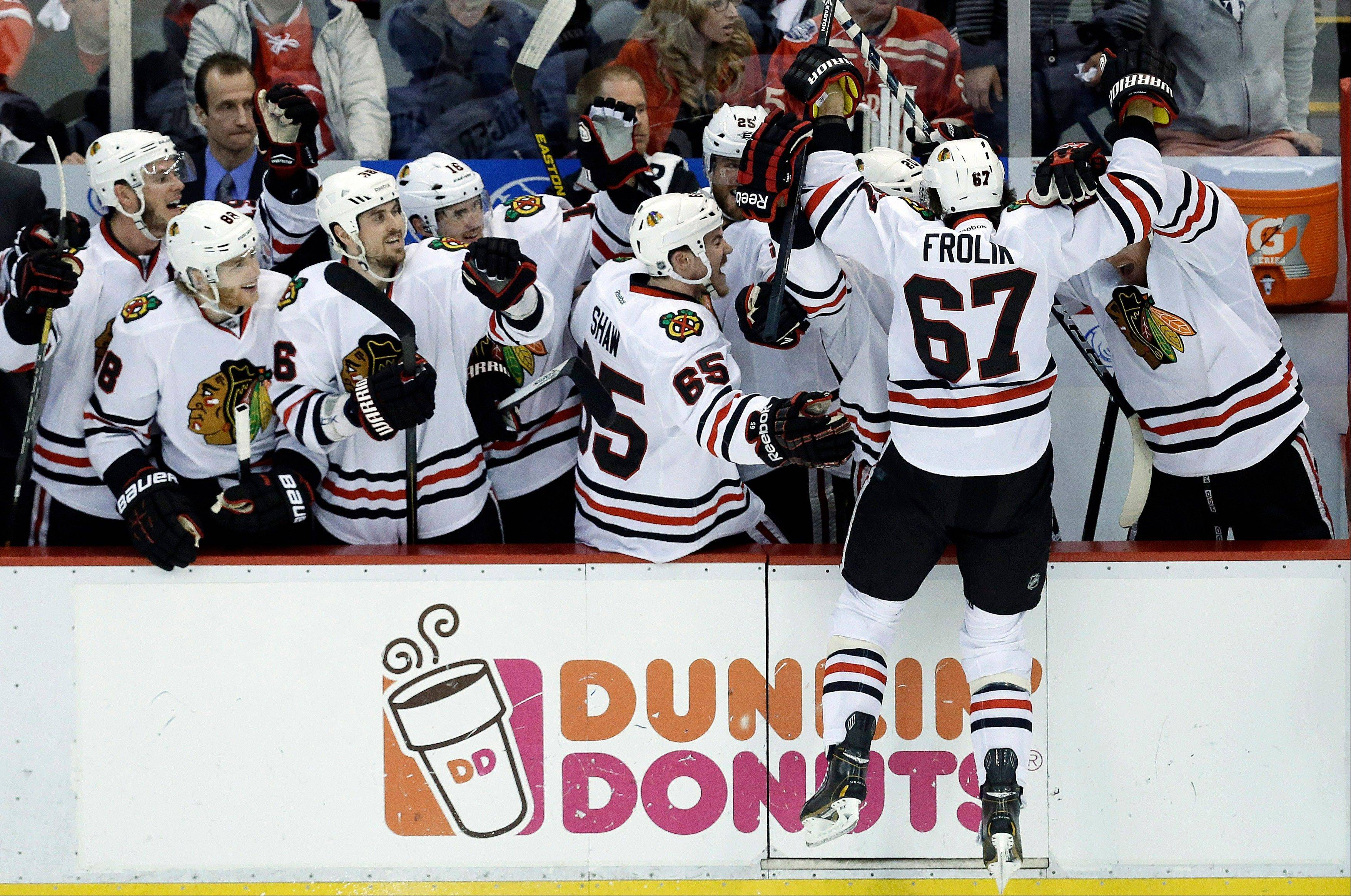 Chicago Blackhawks center Michael Frolik (67), of the Czech Republic, celebrates scoring a penalty shot goal against the Detroit Red Wings goalie Jimmy Howard during the third period in Game 6 of the Western Conference semifinals in the NHL hockey Stanley Cup playoffs in Detroit, Monday, May 27, 2013.