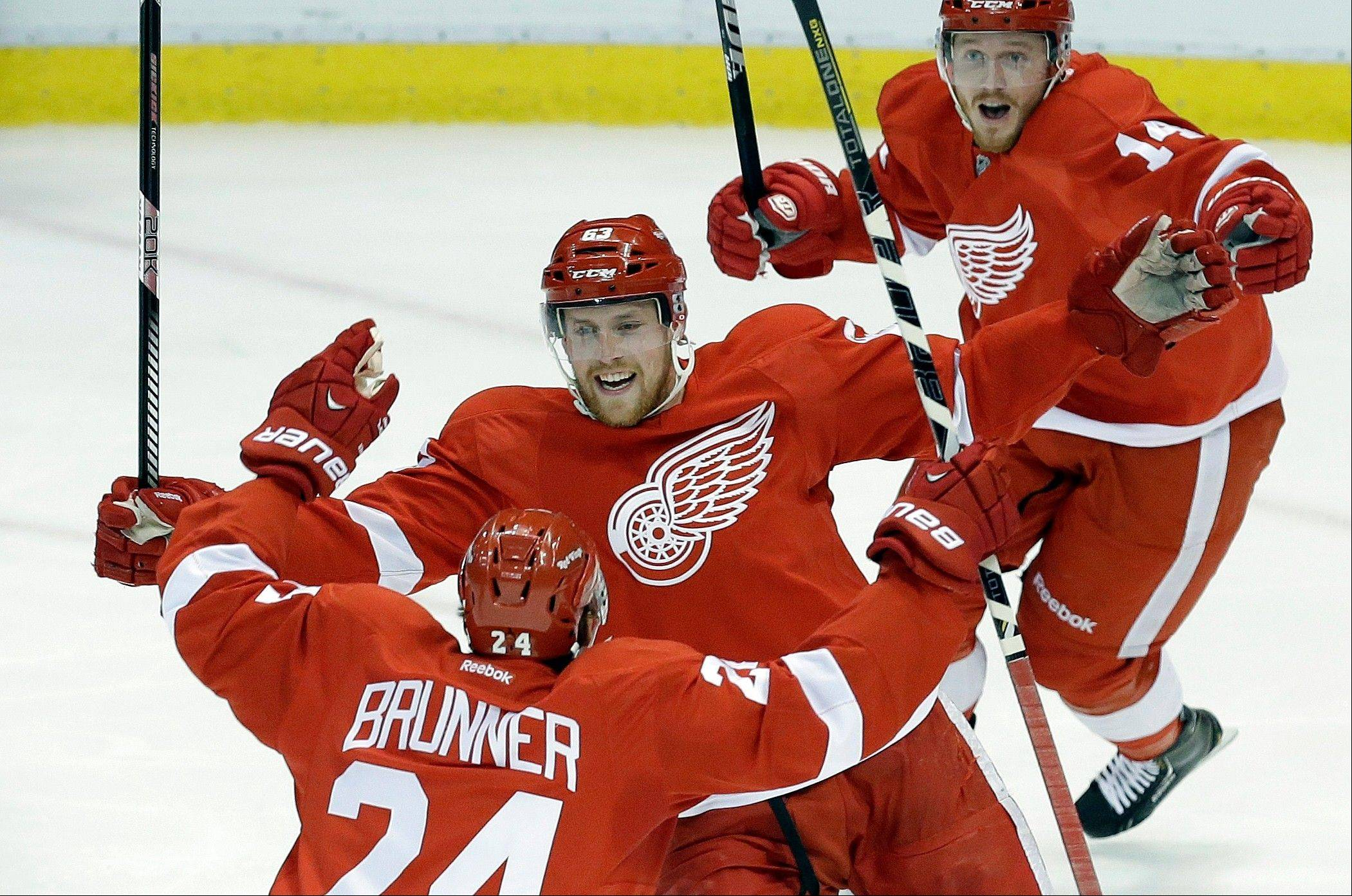 Detroit Red Wings center Joakim Andersson, center, of Sweden, celebrates scoring against the Chicago Blackhawks with Damien Brunner (24), of Switzerland, and Gustav Nyquist (14), of Sweden, during the second period in Game 6 of the Western Conference semifinals in the NHL hockey Stanley Cup playoffs in Detroit, Monday, May 27, 2013.