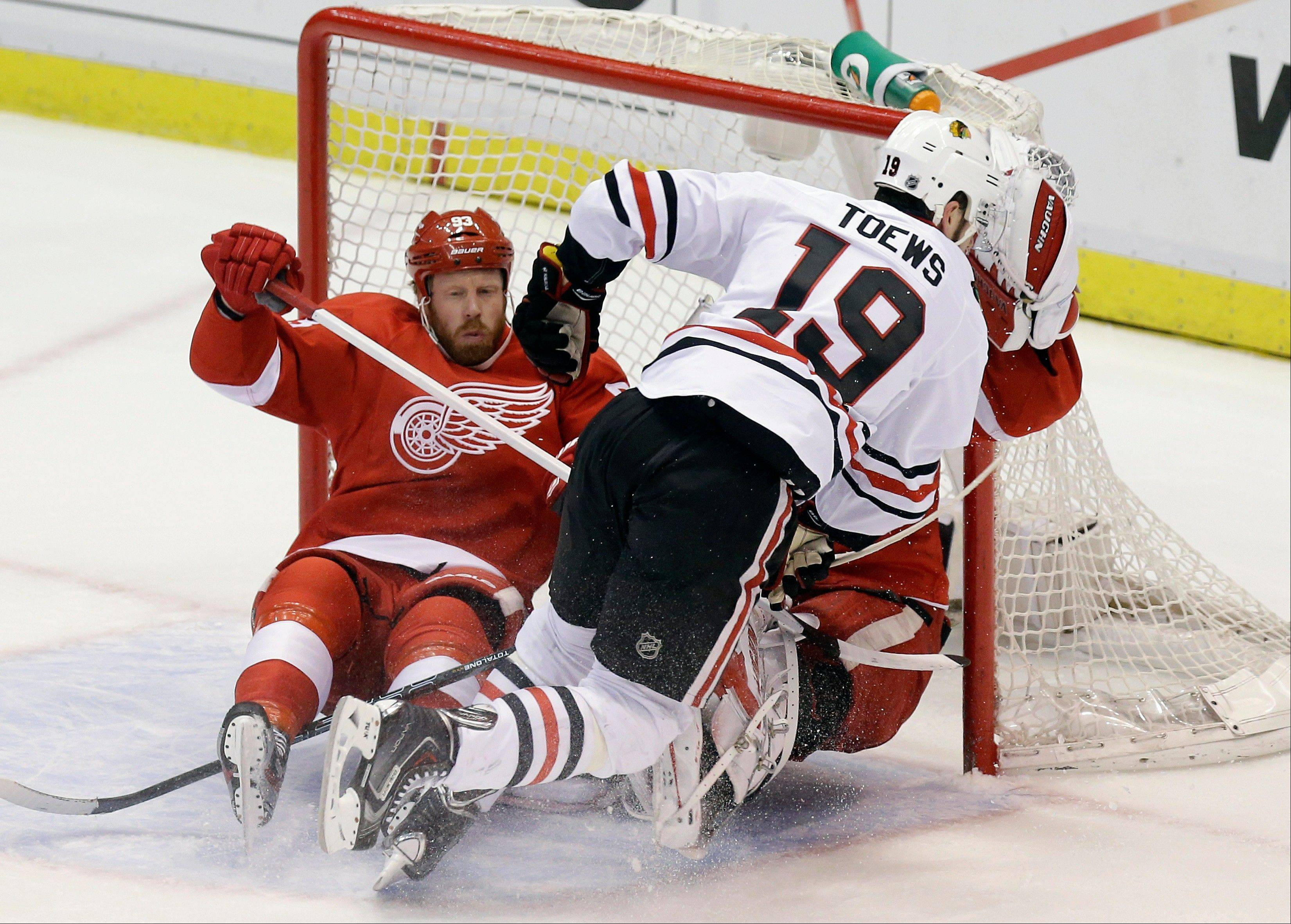 Chicago Blackhawks center Jonathan Toews (19) crashes into Detroit Red Wings goalie Jimmy Howard and left wing Johan Franzen (93), of Sweden, left, during the first period of Game 6 of the NHL hockey Stanley Cup playoffs Western Conference semifinals in Detroit, Monday, May 27, 2013.
