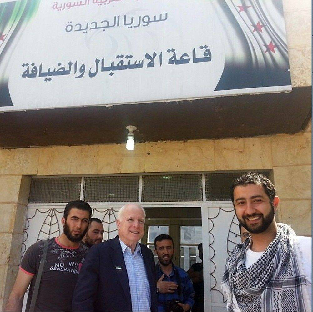 Sen. John McCain, center, accompanied by Mouaz Moustafa, right, visits rebels in Syria Monday. McCain, who slipped into the country for a surprise visit, favors providing arms to rebel forces in Syria.