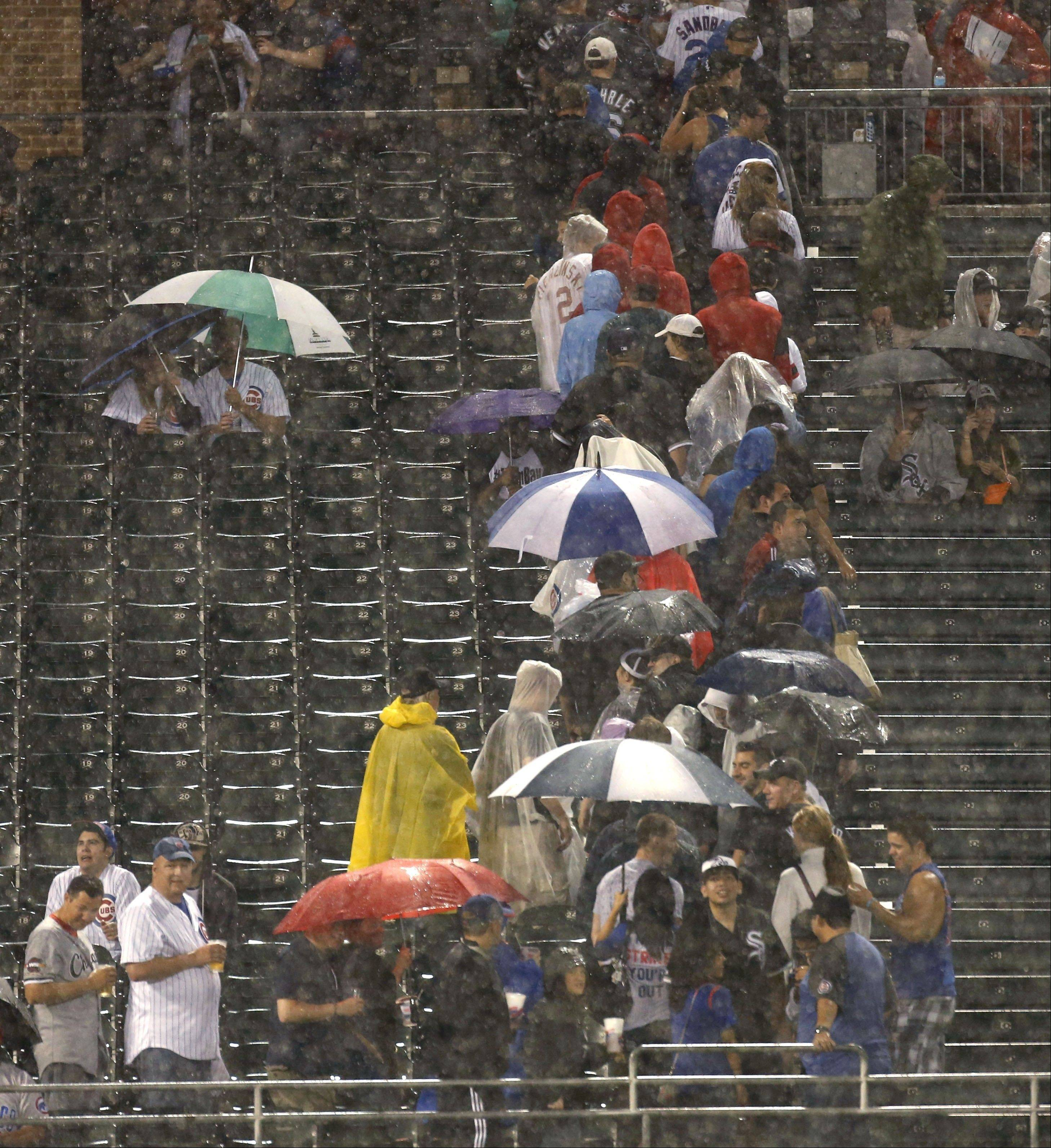 Some baseball fans seek shelter during a downpour in the third inning of an interleague baseball game between the Chicago White Sox and the Chicago Cubs on Tuesday, May 28, 2013, in Chicago. (AP Photo/Charles Rex Arbogast)