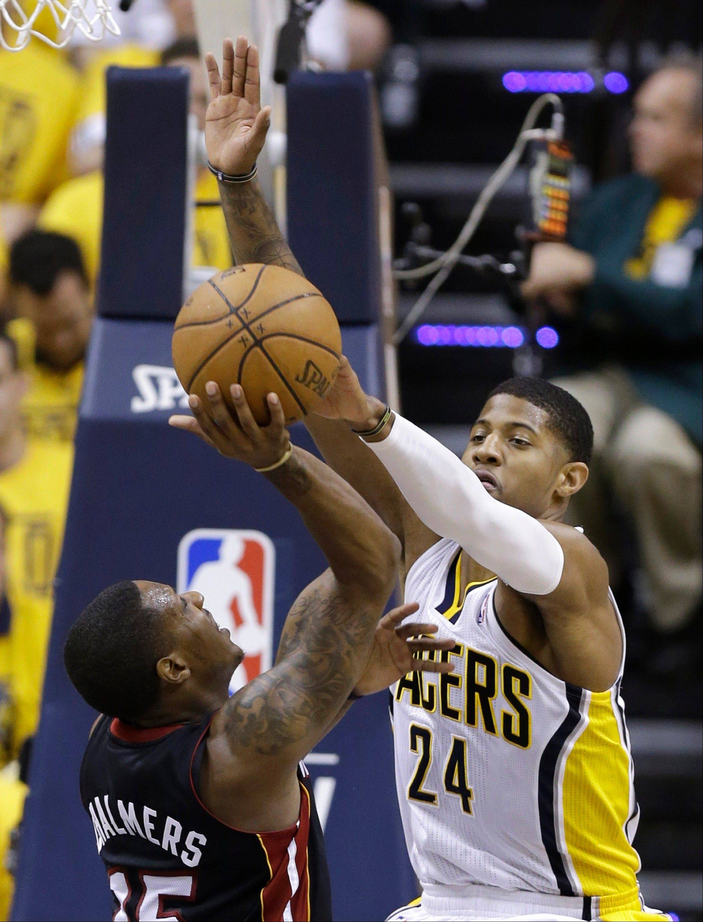 Miami Heat's Mario Chalmers has his shot blocked by Indiana Pacers' Paul George (24) during the second half of Game 4 of the NBA basketball Eastern Conference finals, Tuesday, May 28, 2013, in Indianapolis. (AP Photo/Michael Conroy)