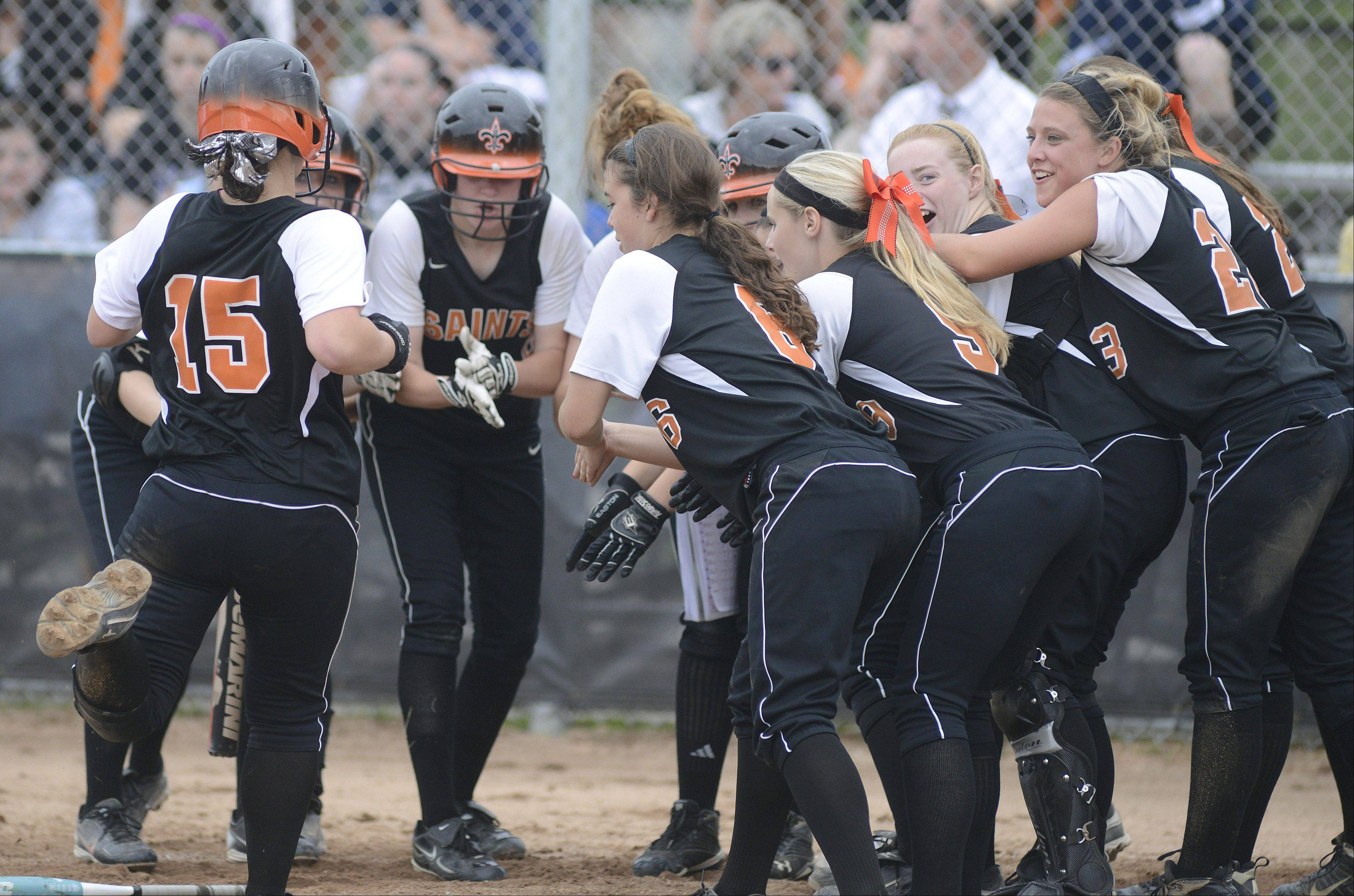 St. Charles East�s Alex Latoria is welcomed at home plate after hitting a home run in the sixth inning of the Saints� Class 4A sectional semifinal win over Bartlett on Tuesday in St. Charles.
