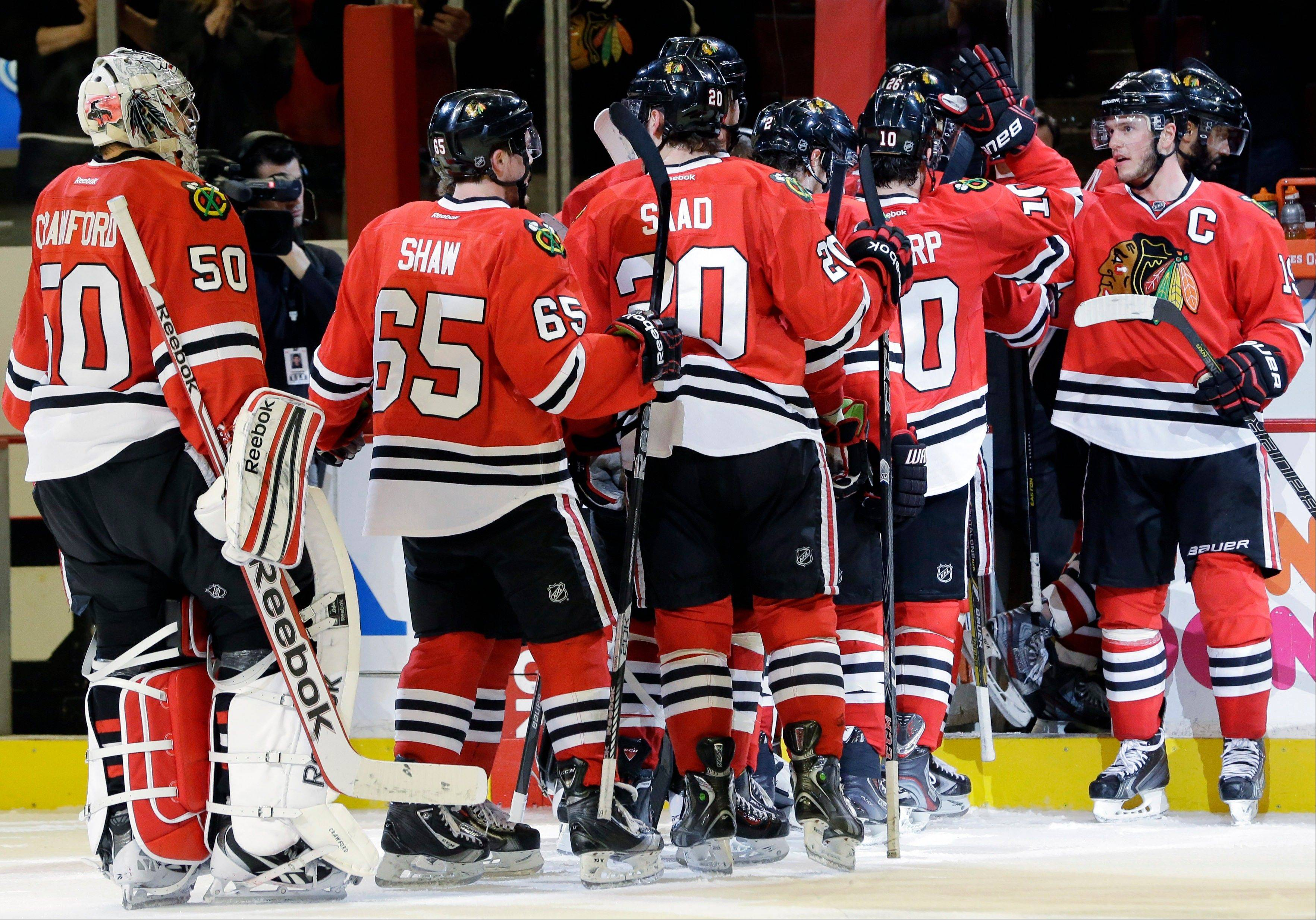 Captain Jonathan Toews, far right, and the Blackhawks hope to be celebrating again Wednesday night after their Game 7 against Detroit.