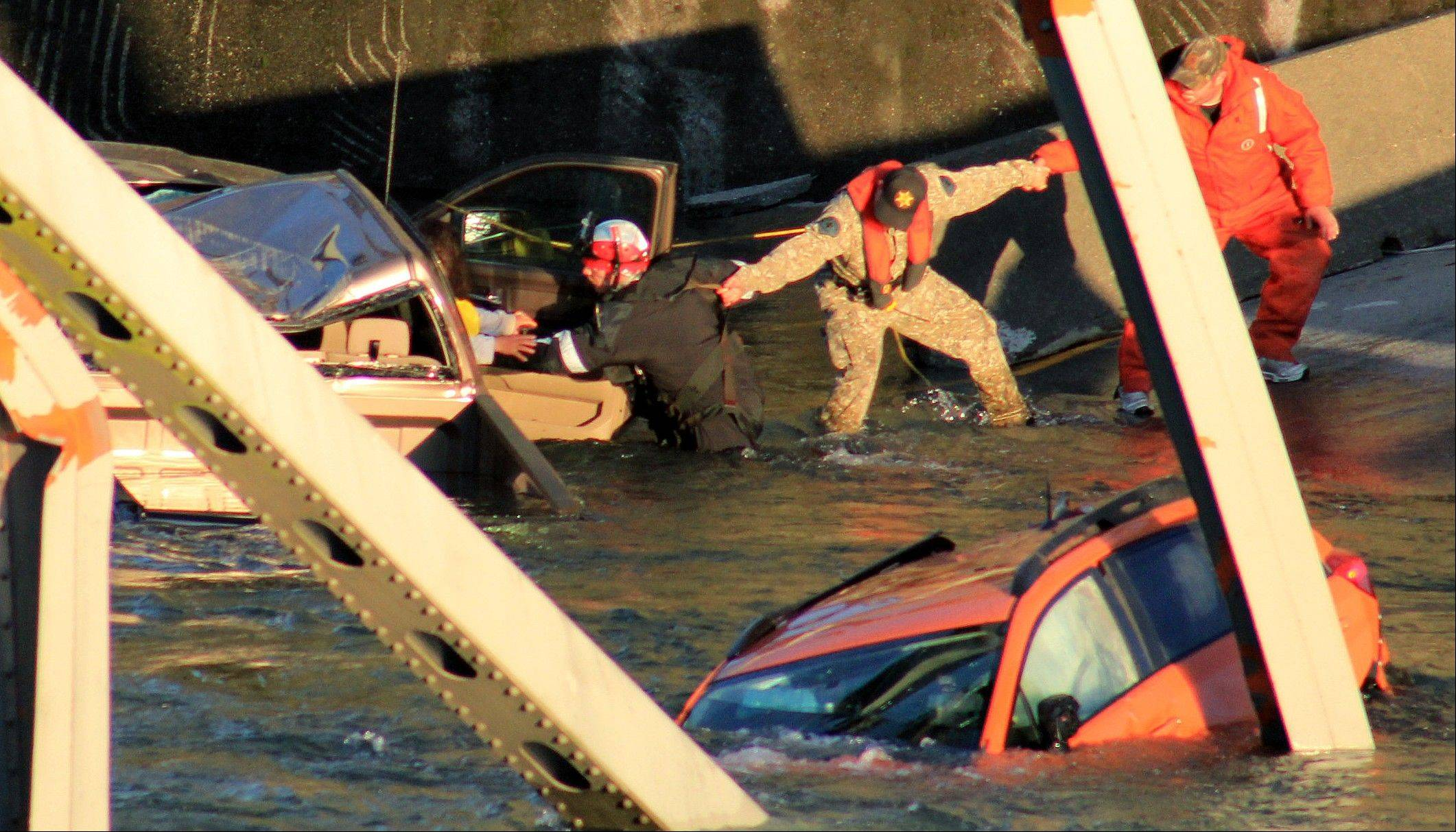 Rescue workers form a human chain as they begin to remove a woman who reaches out from a smashed pickup truck that fell into the Skagit River after the collapse of the Interstate 5 bridge Thursday, May 23, 2013, in Mount Vernon, Wash.