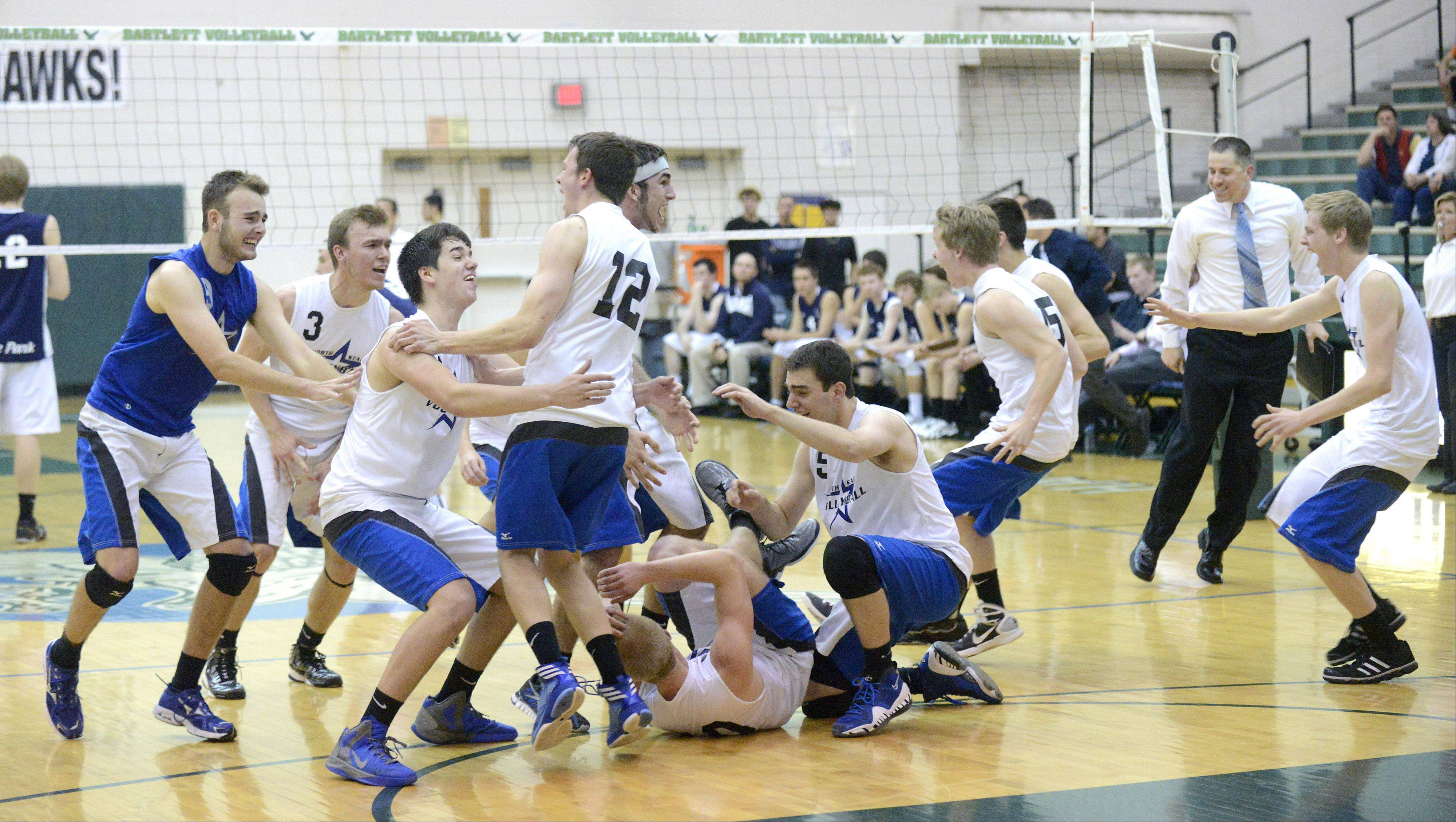St. Charles North's Jack Harbaugh prepares to lift teammate Jake Hamilton (12) into the air as Kevin Beach rolls on the floor as the North Stars celebrate their sectional championship over Lake Park at Bartlett on Tuesday.