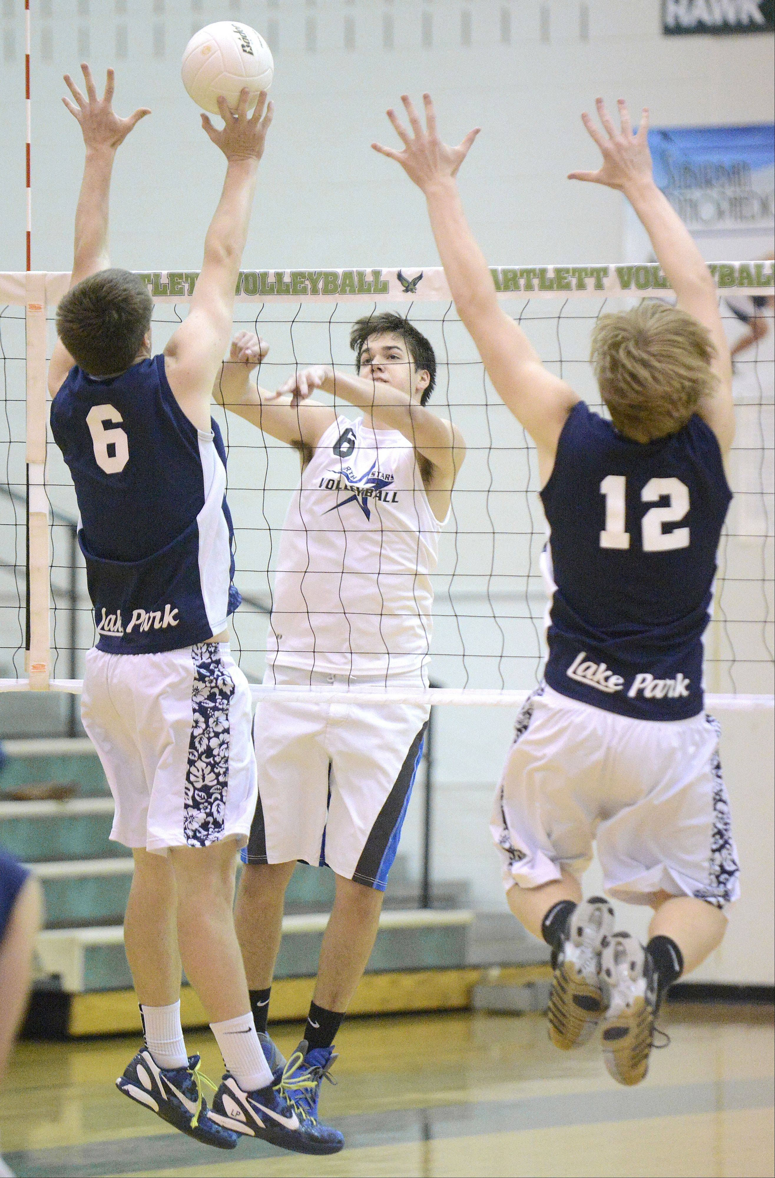 Lake Park's Dillon Hock and Derek Burke attempt a block on a spike by St. Charles North's Jack Harbaugh in the first game of sectional championship play in Bartlett on Tuesday.